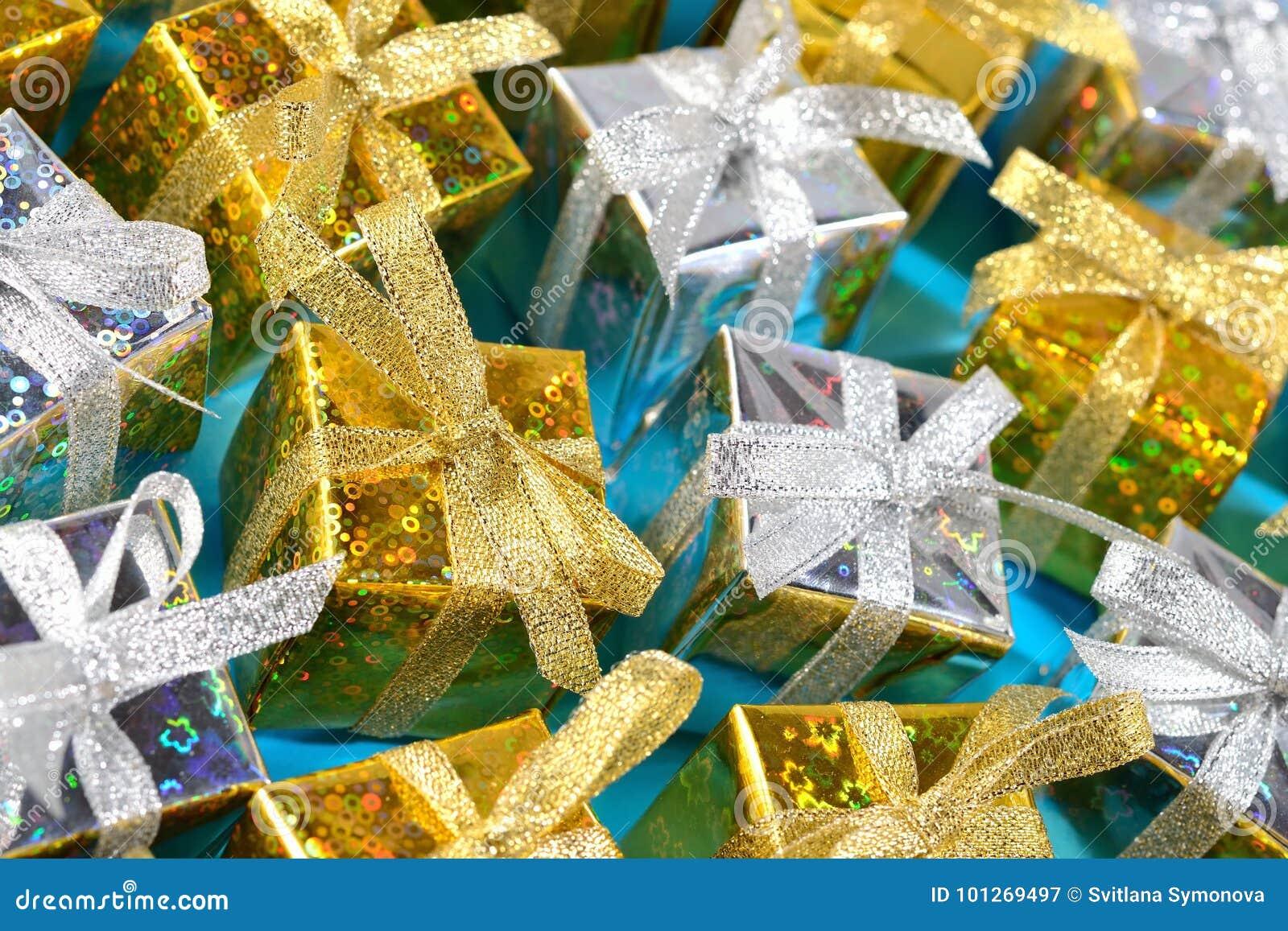 Vista superior del primer de oro y de plata de los regalos en un azul