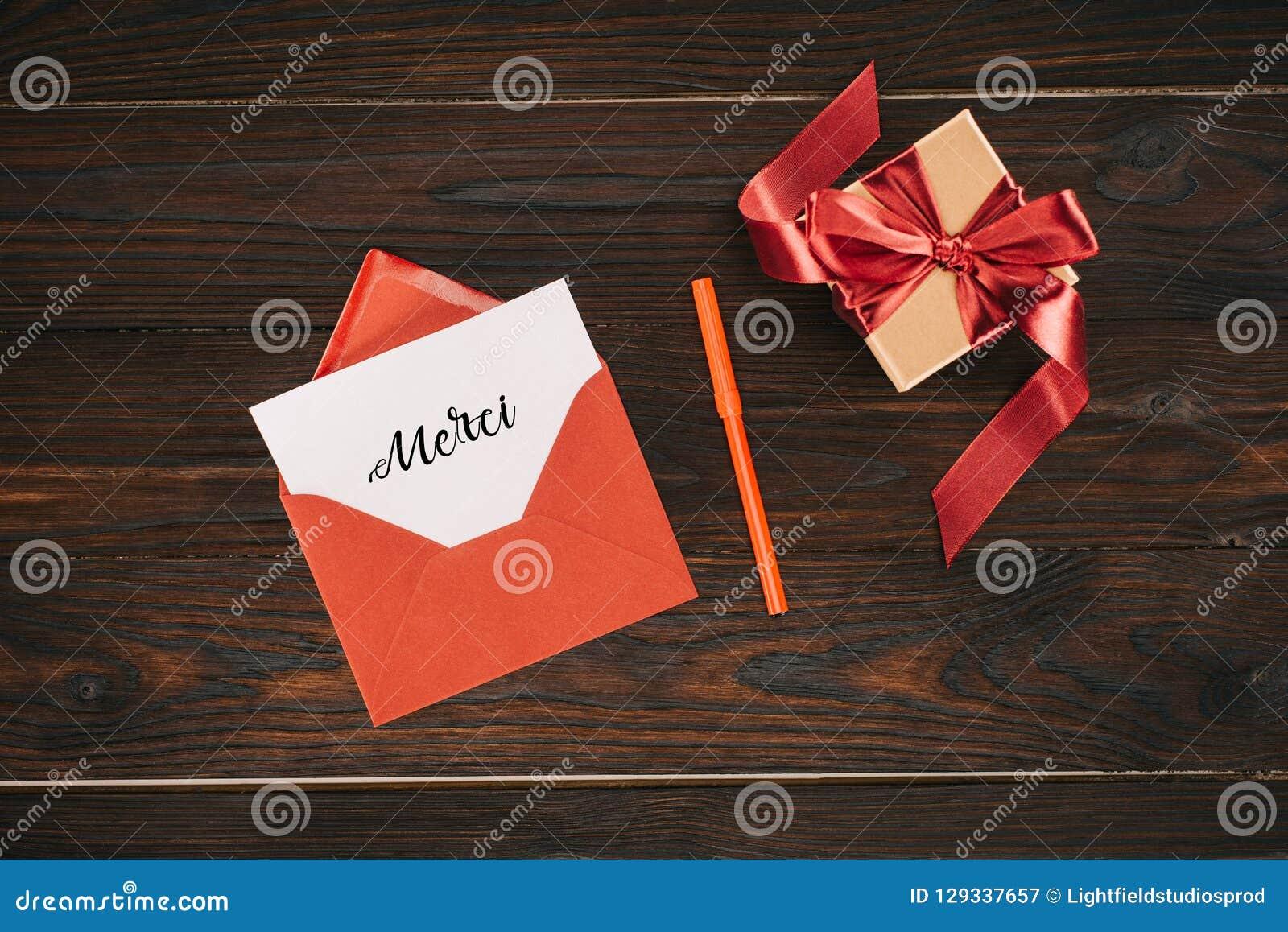 Vista superior del sobre rojo con las letras del merci en la caja del papel y de regalo