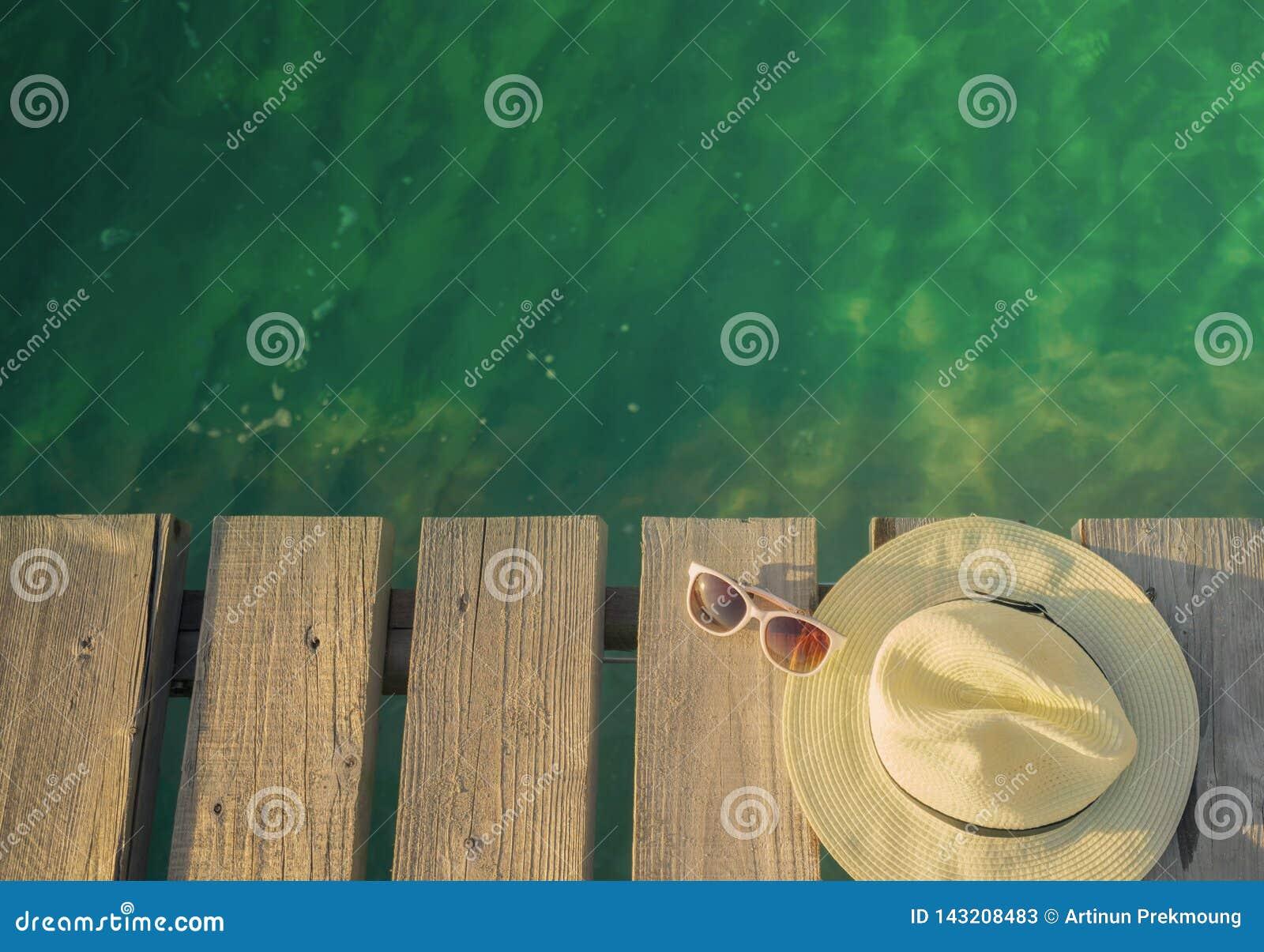 Vista superior do chapéu e dos óculos de sol de palha na ponte de madeira sobre a água do mar verde esmeralda Fundo do curso das