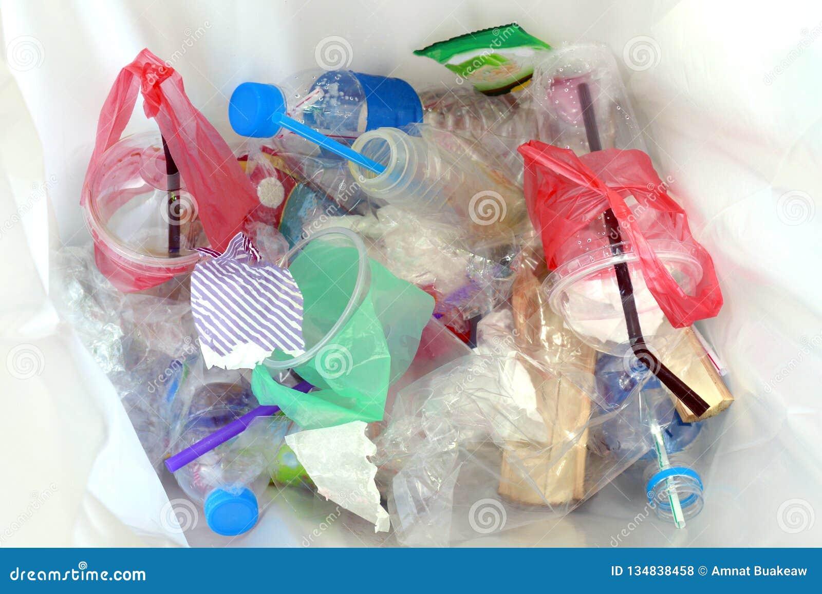 Vista superior do desperdício e de palhas plásticos da bebida da água de garrafa na reciclagem suja, na pilha da garrafa plástica