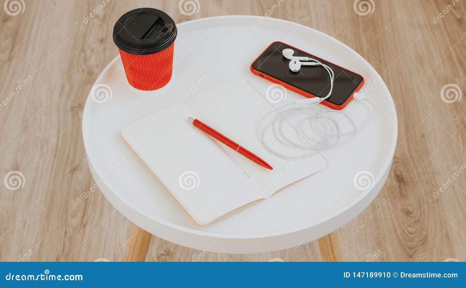 Vista superior do papel de nota vazio vazio aberto com pena, a xícara de café, o telefone e os fones de ouvido vermelhos na tabel