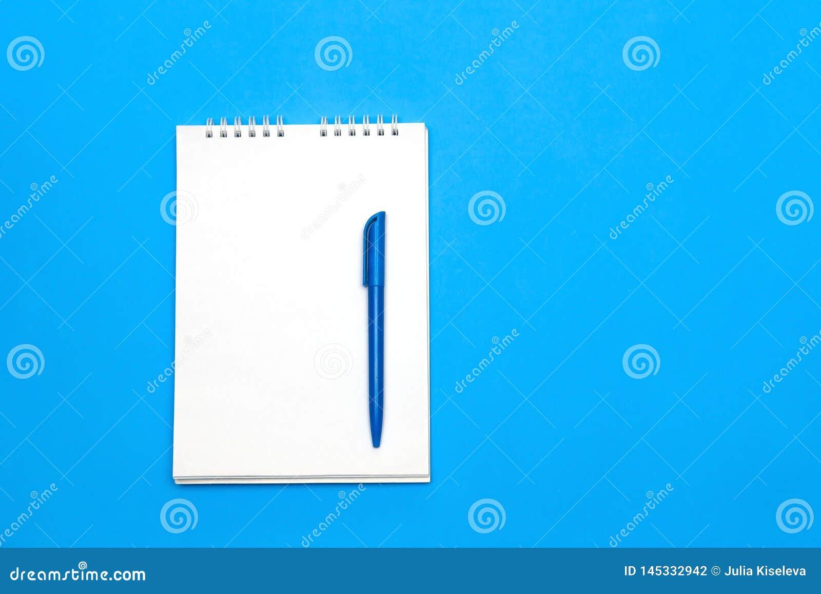 Vista superior do papel de nota vazio com a pena na tabela de madeira azul para o fundo