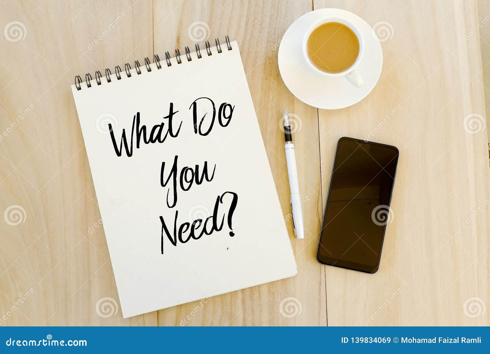 Vista superior do telefone celular, da pena, de uma xícara de café, e do caderno escrito com pergunta o que você precisam? Concei