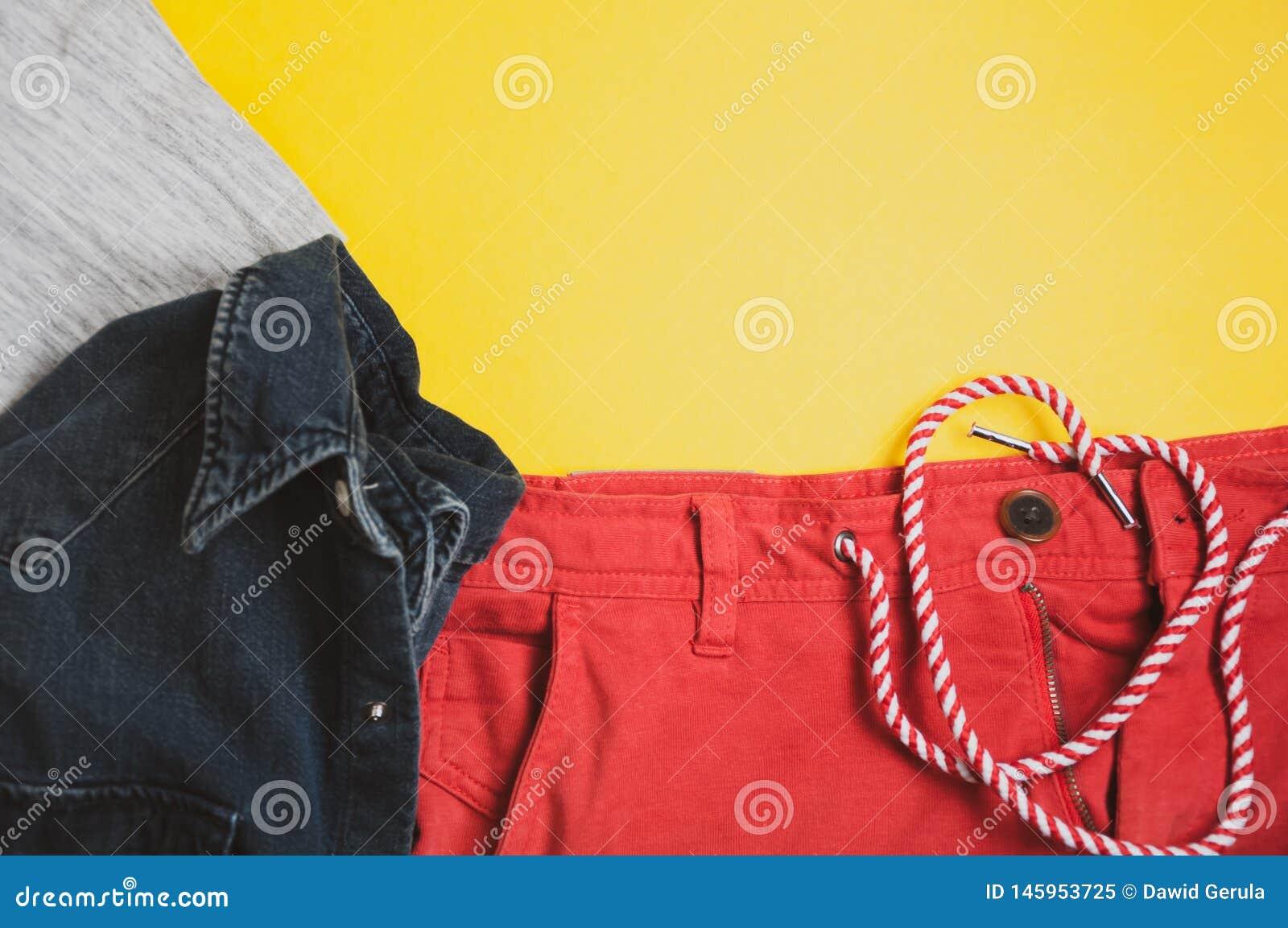 Vista superior do tshirt cinzento, do revestimento da sarja de Nimes e do short vermelho no fundo amarelo