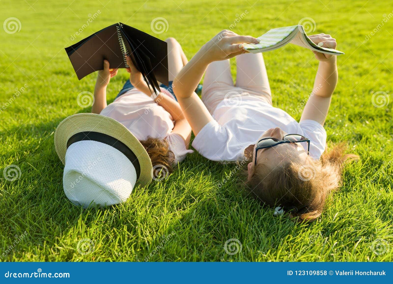 Vista superior, dois livros de leitura novos dos estudantes fêmeas que encontram-se na grama verde
