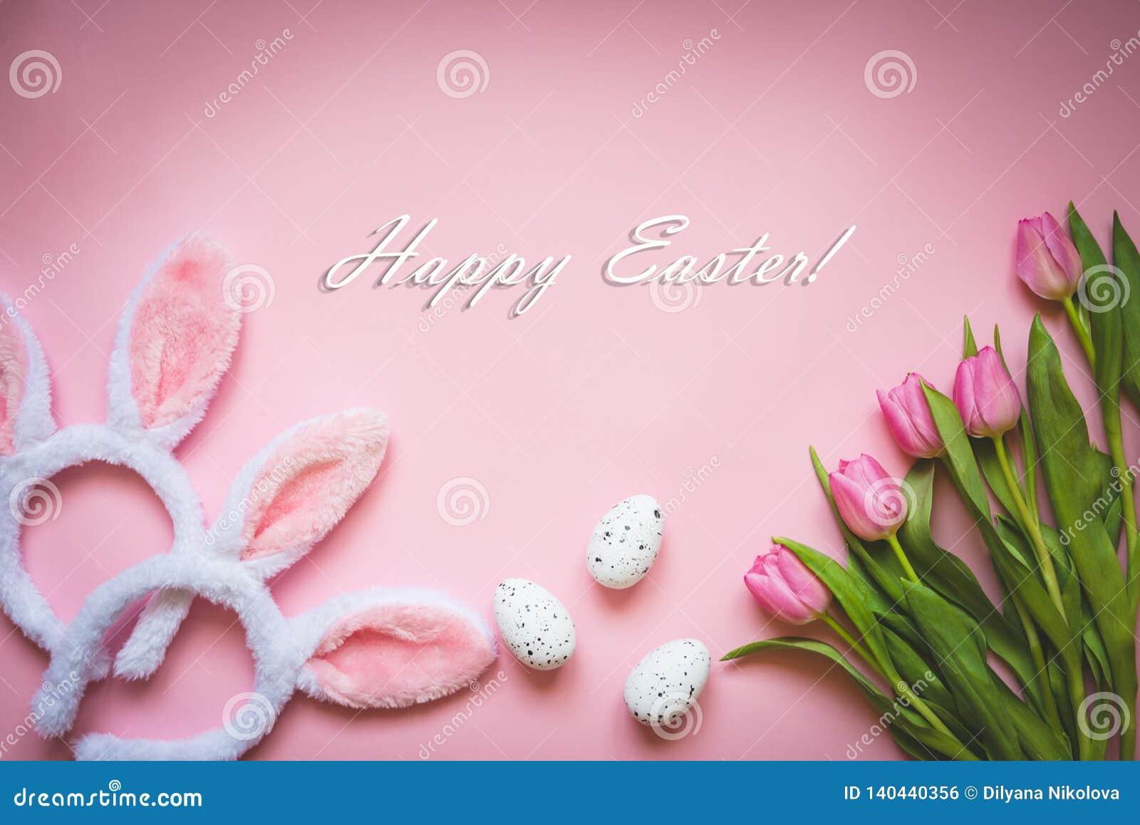 Vista superior dos ovos da páscoa, de tulipas cor-de-rosa e de duas orelhas macias brancas do coelho sobre o fundo cor-de-rosa Fu