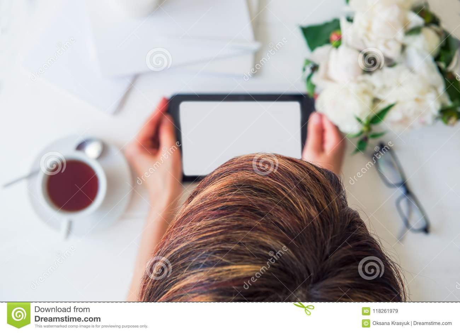 A vista superior focalizou a cabeça do ` s da menina com espaço de trabalho borrado com as mãos que guardam a tabuleta, copo do c