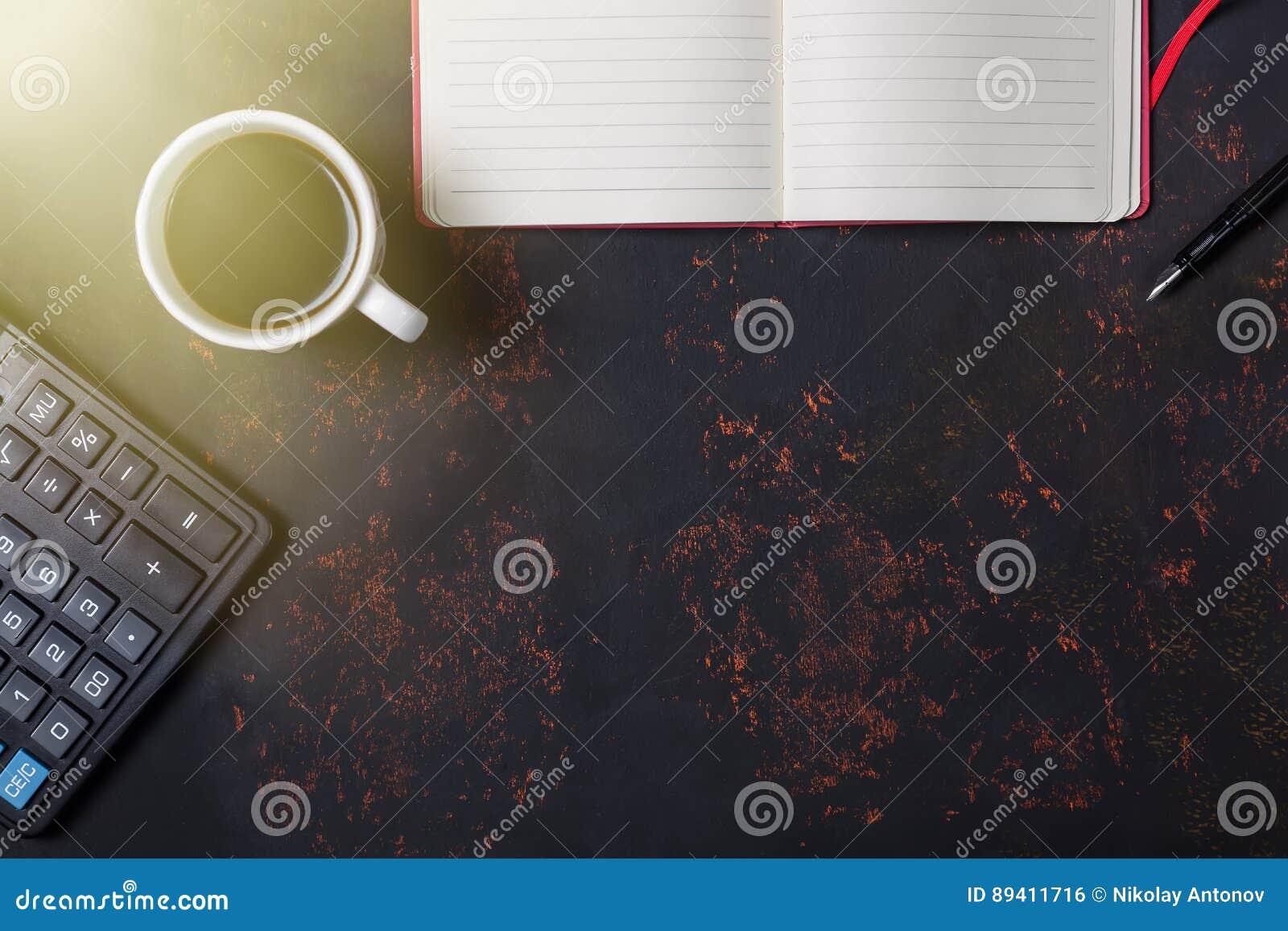 Vista superior um a xícara de café com caderno, pena de fonte e calculadora no fundo de pedra oxidado com espaço livre