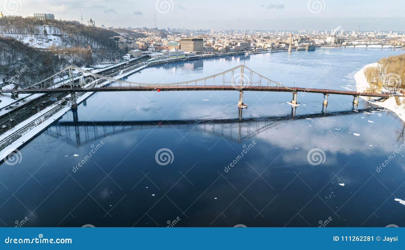 Vista superiore aerea del pedone e del vicolo della pista ciclabile sul ponte del parco nell inverno e del fiume di Dnieper da so