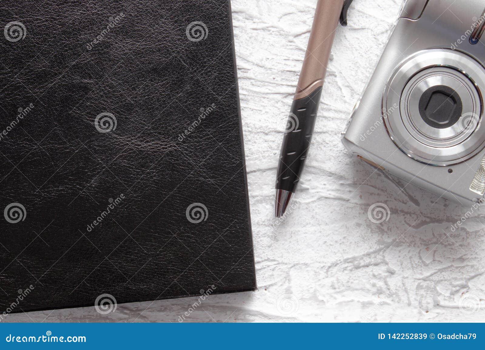 Vista superiore del taccuino e della penna neri vicino alla macchina fotografica della foto sul fondo bianco dello scrittorio per