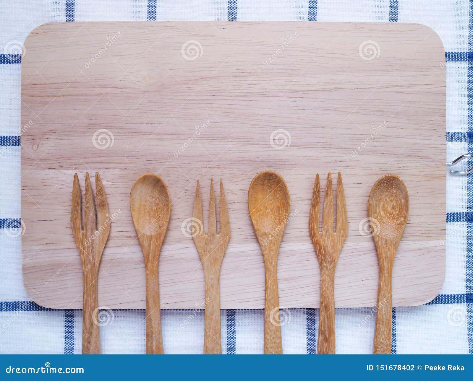 Vista superiore della coltelleria, del cucchiaio e della forchetta di legno sul tagliere