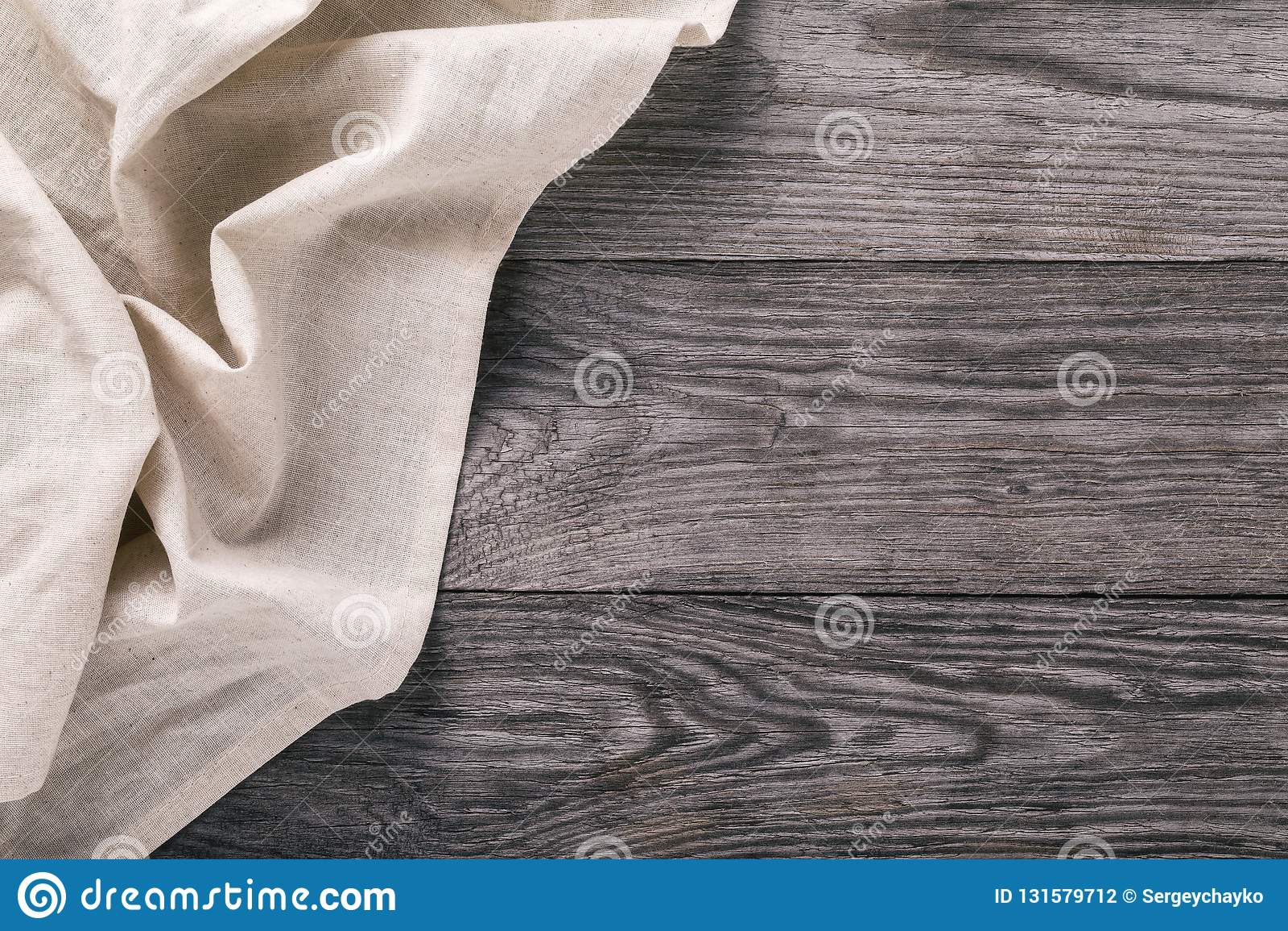 Vista superiore della tovaglia leggera sul lato sinistro della tavola di legno