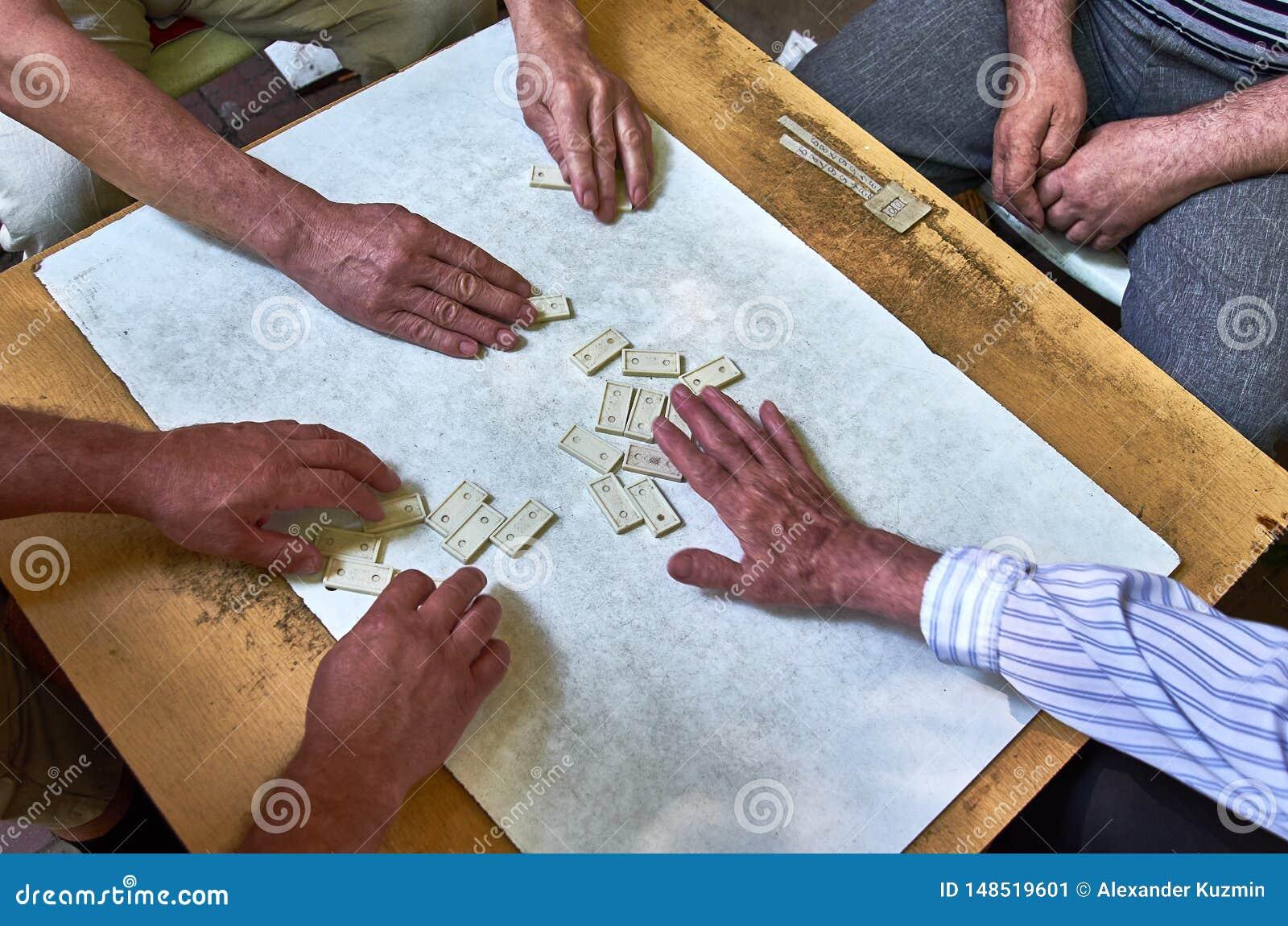 Vista superiore delle mani della gente che gioca i domino