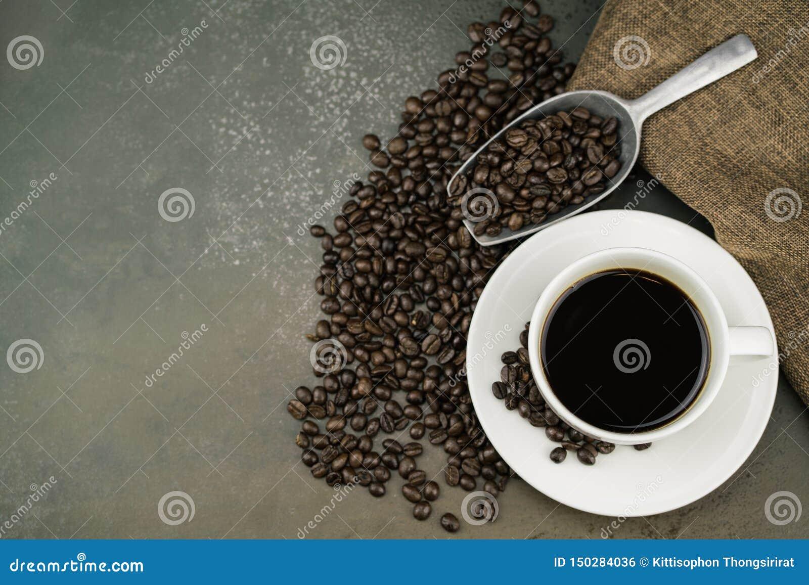 Vista superiore di caffè caldo nella tazza bianca con i chicchi, la borsa ed il mestolo di caffè dell arrosto sul fondo di pietra