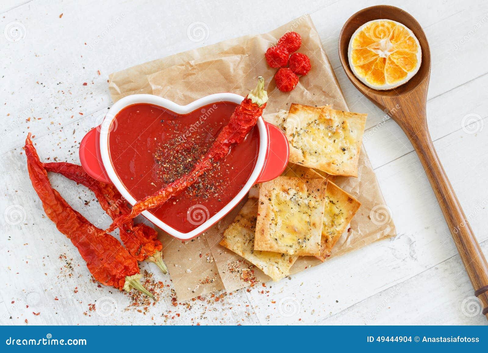 Vista superiore di una minestra piccante del pomodoro con i cracker del formaggio e del peperoncino