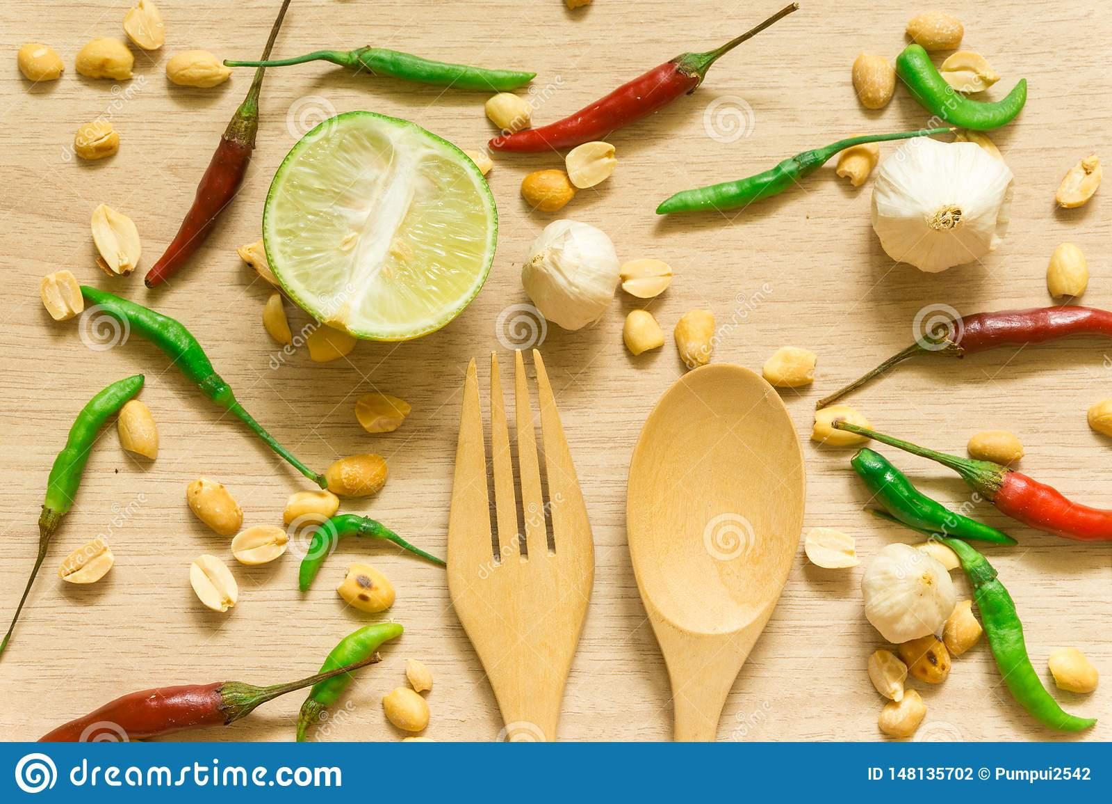 Vista superiore di vari ortaggi freschi paprica, arachide, aglio, limone ed erbe isolati su fondo di legno