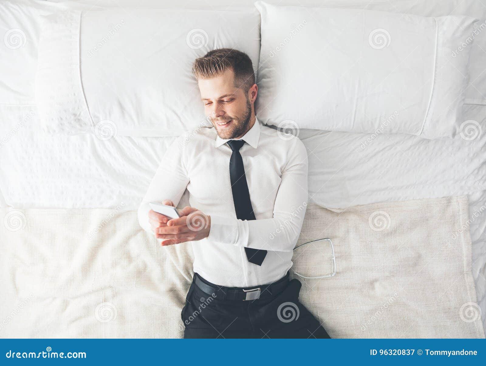 Vista superiore Uomo d affari bello che si trova sul letto che manda un sms dal suo smartphone