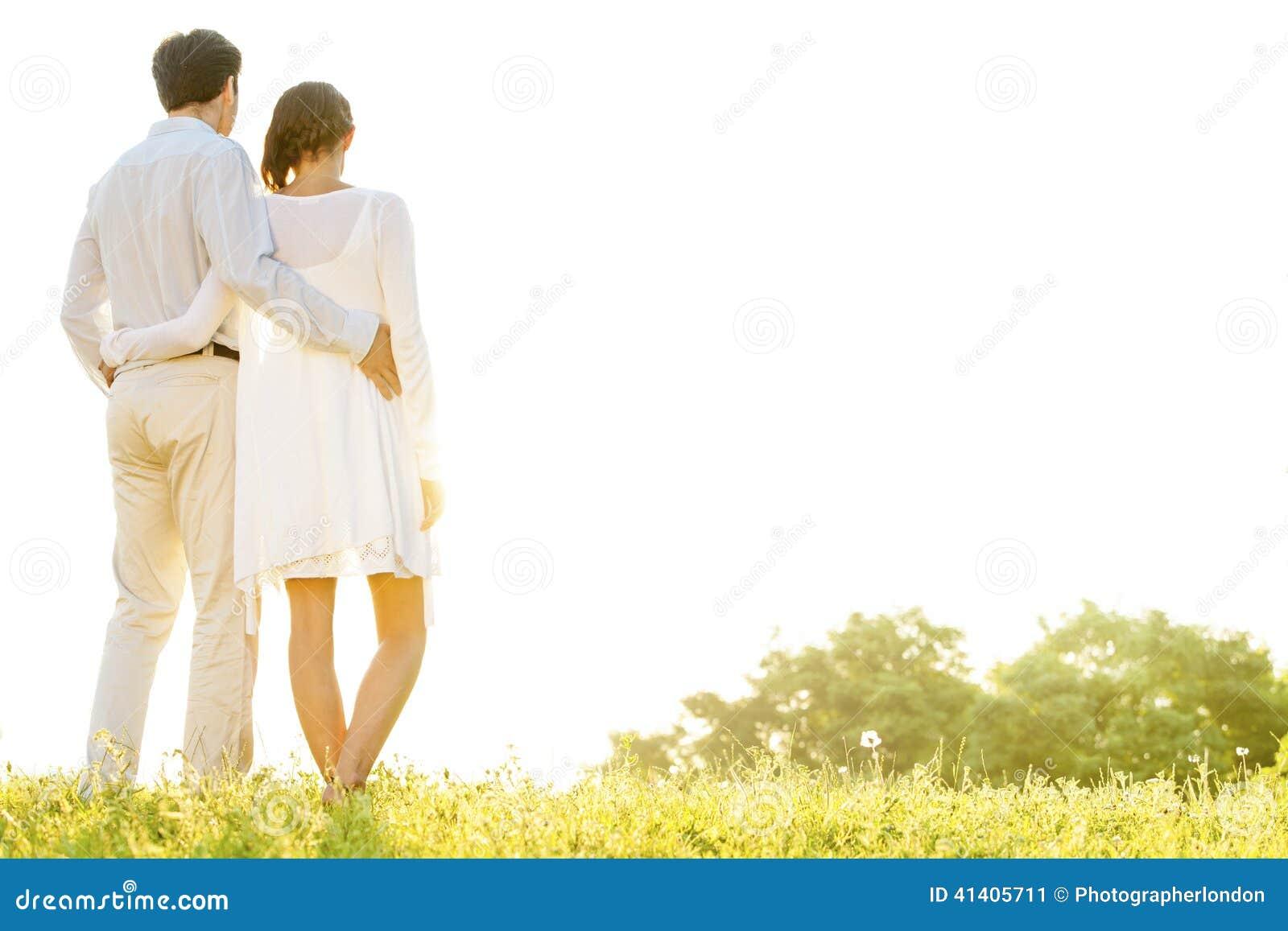 Vista traseira dos braços eretos dos pares loving ao redor contra o céu claro