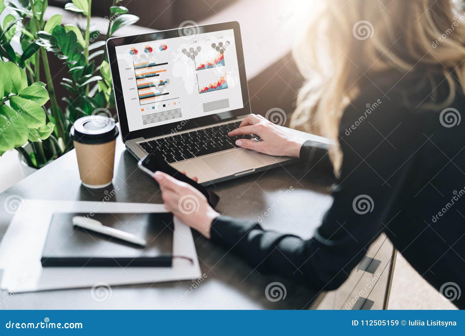 Vista traseira A mulher de negócios nova está trabalhando no portátil com gráficos, cartas, diagramas, programações na tela Merca