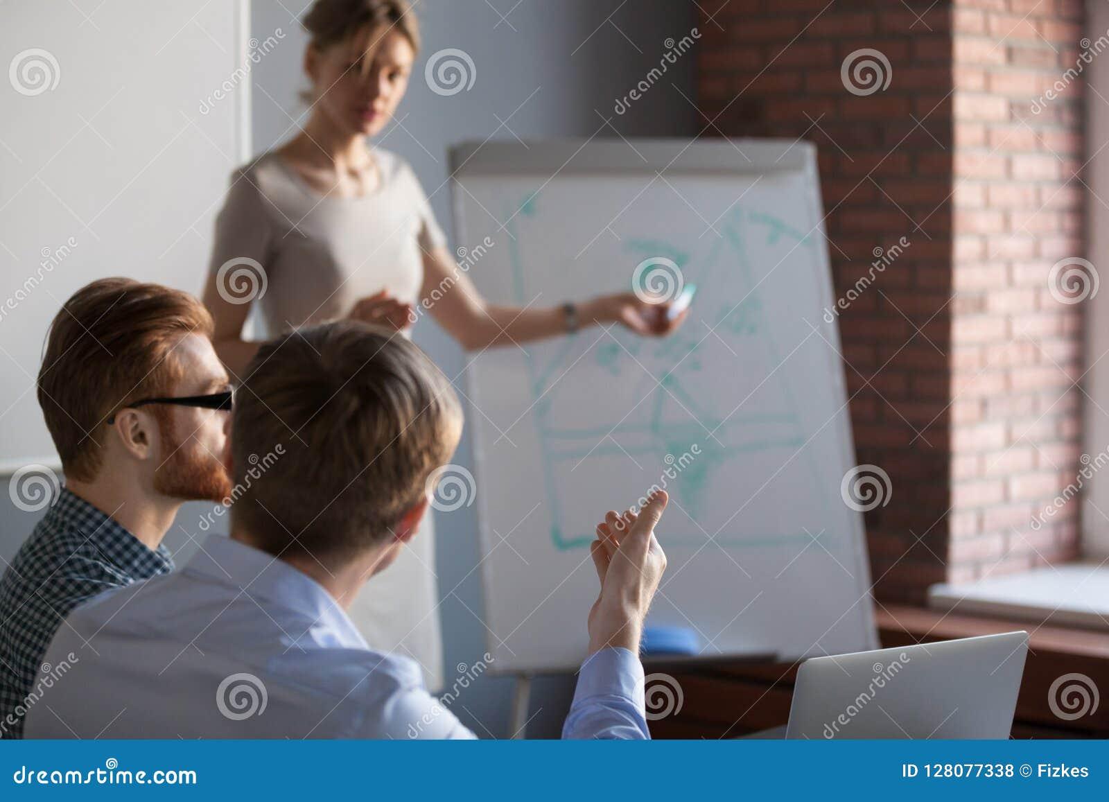 Vista traseira no homem de negócios que faz a pergunta ao orador no treinamento
