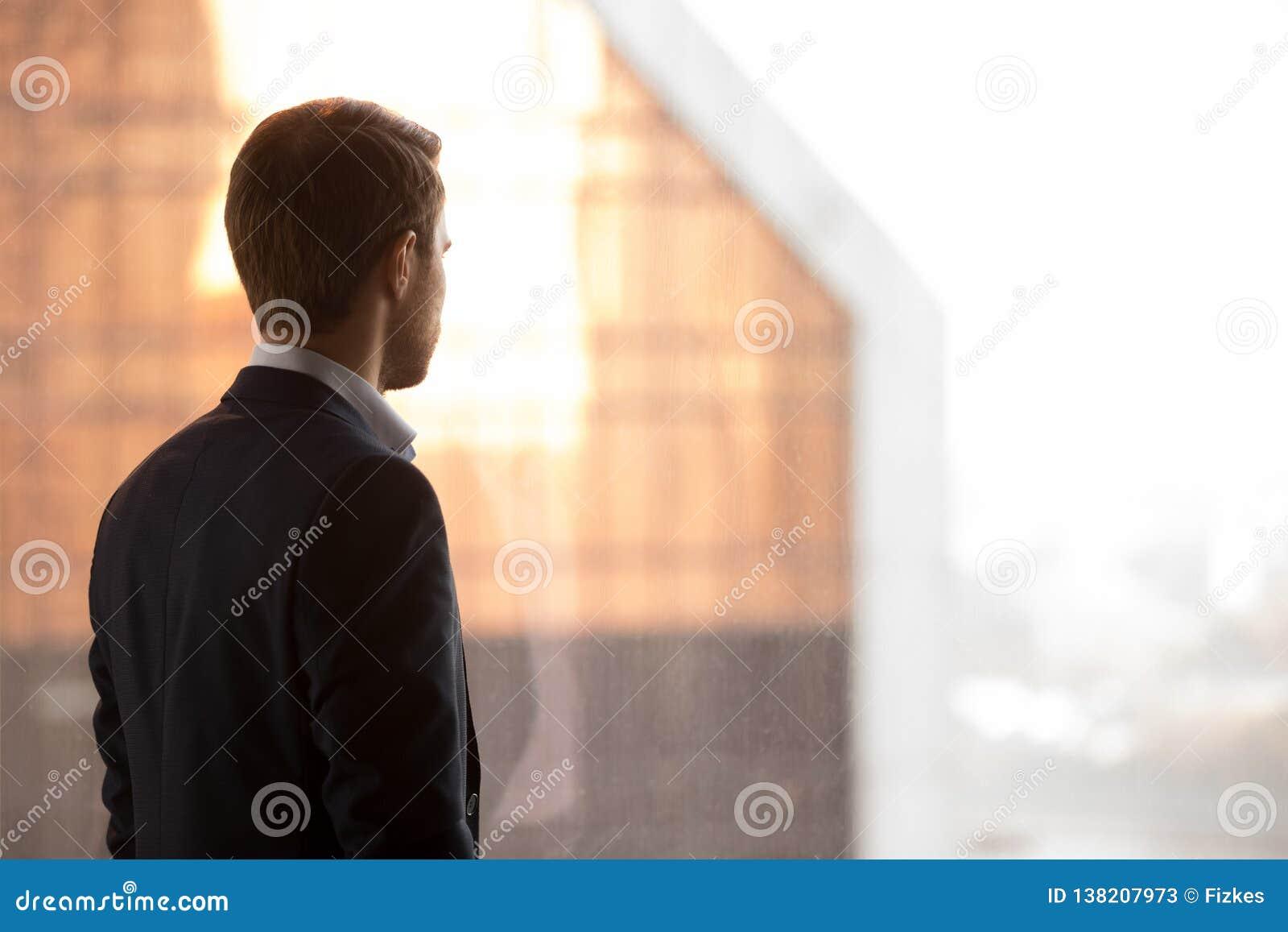 Vista traseira no homem de negócios rico que está para trás de vista a janela