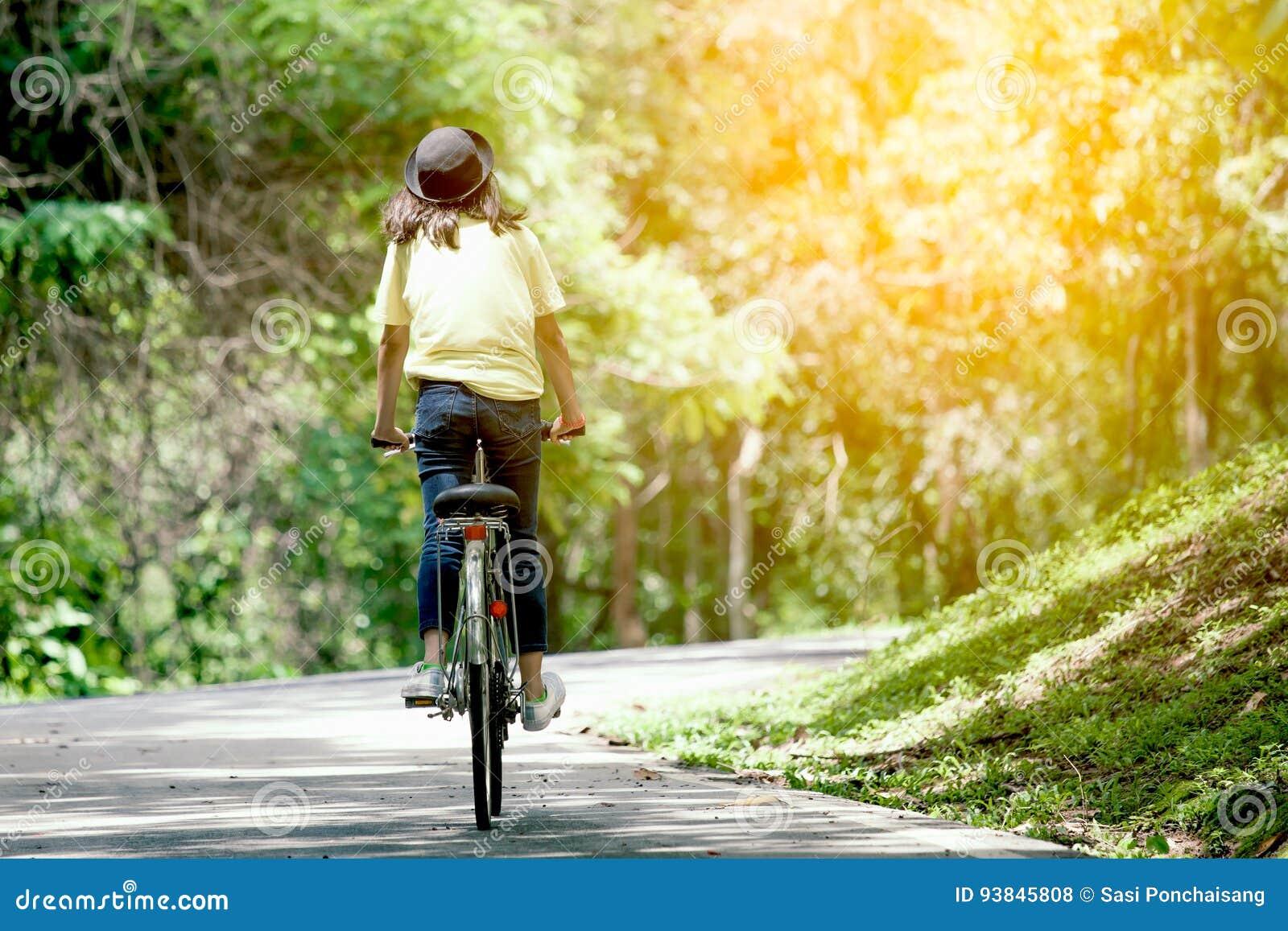 Vista trasera de la bicicleta del montar a caballo de la chica joven en el jardín