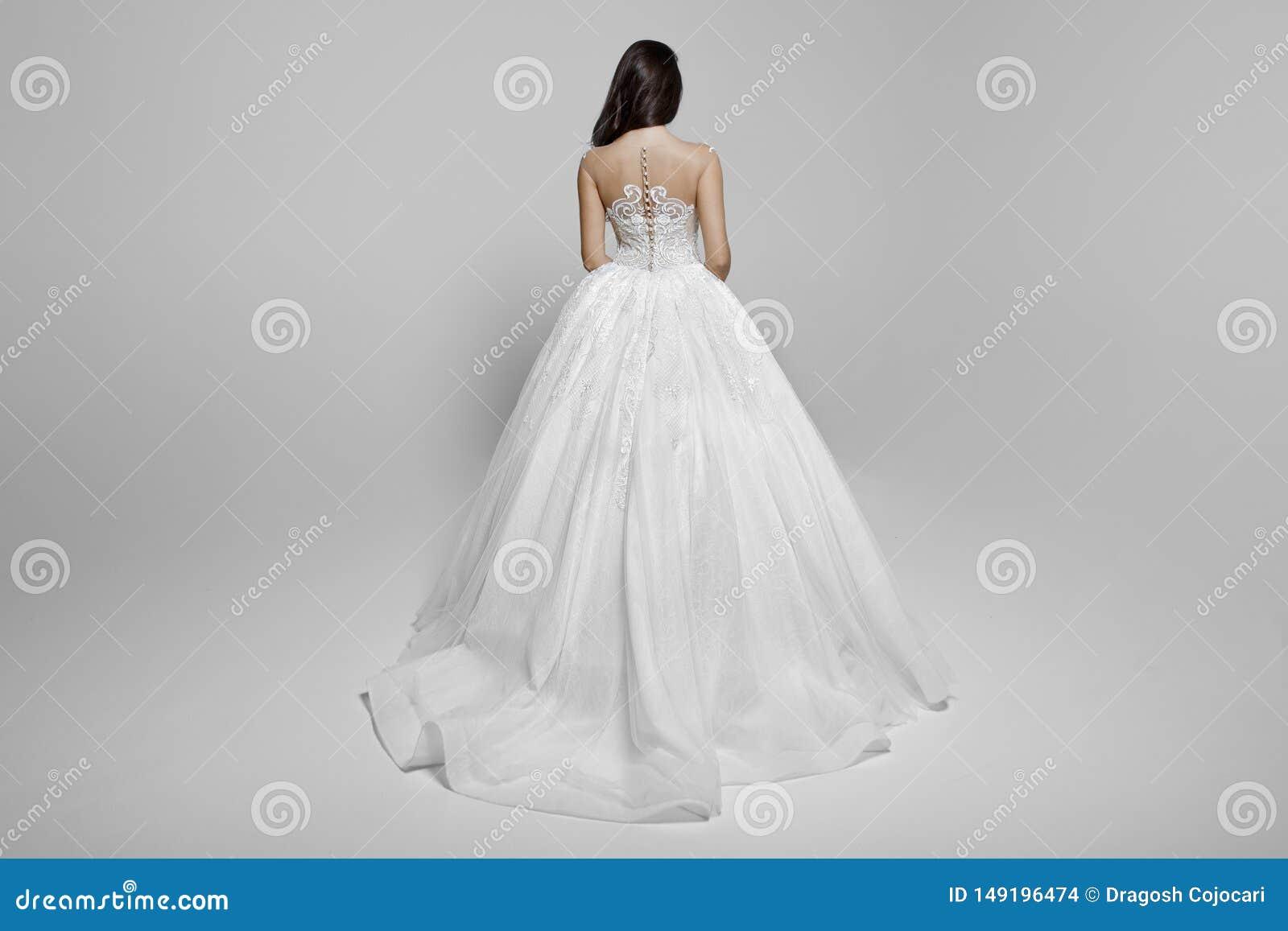 Vista trasera de un modelo femenino moreno del superbe en un vestido de boda blanco de la princesa, en un fondo blanco