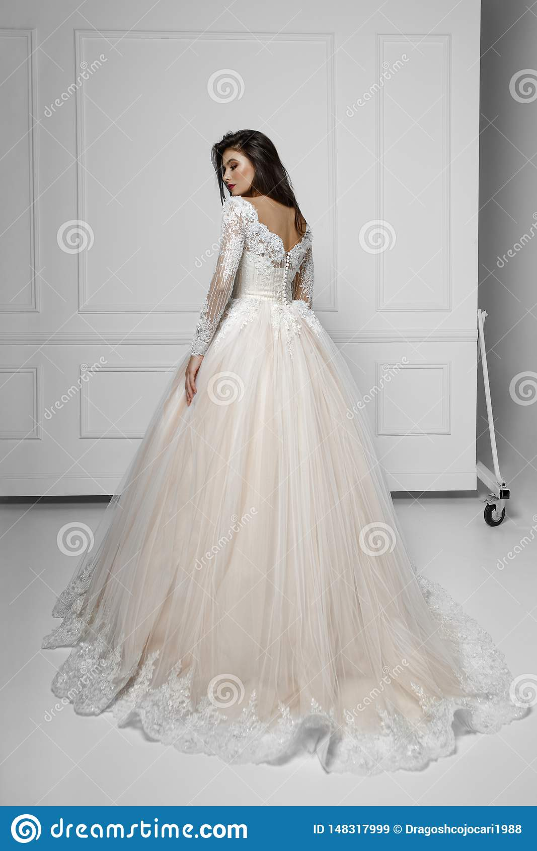 Vista trasera de un modelo de la morenita de la moda en vestido que se casa largo hermoso, cerca de la pared blanca, tiro en el e