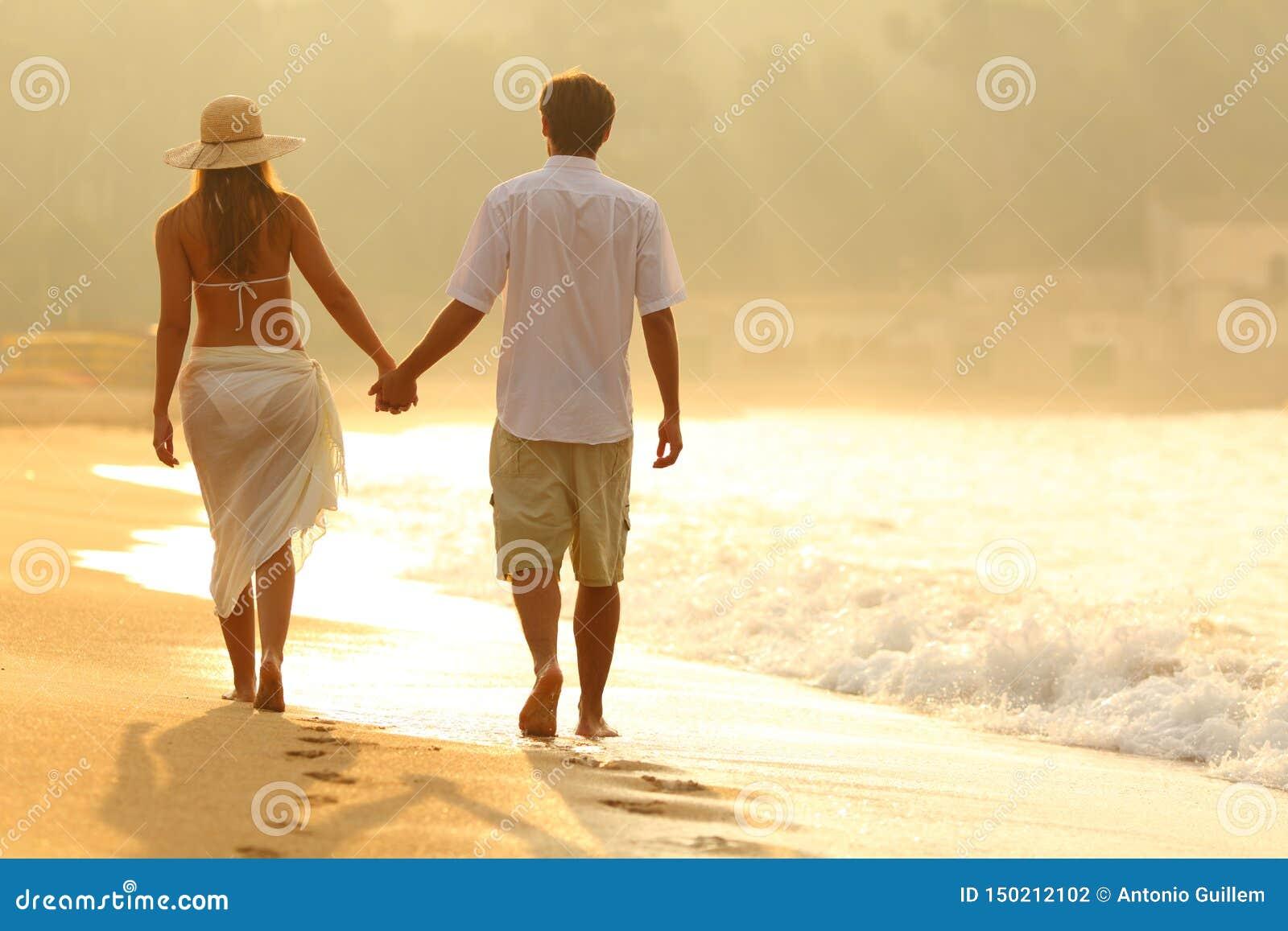 Vista trasera de un par que camina en la playa en la salida del sol