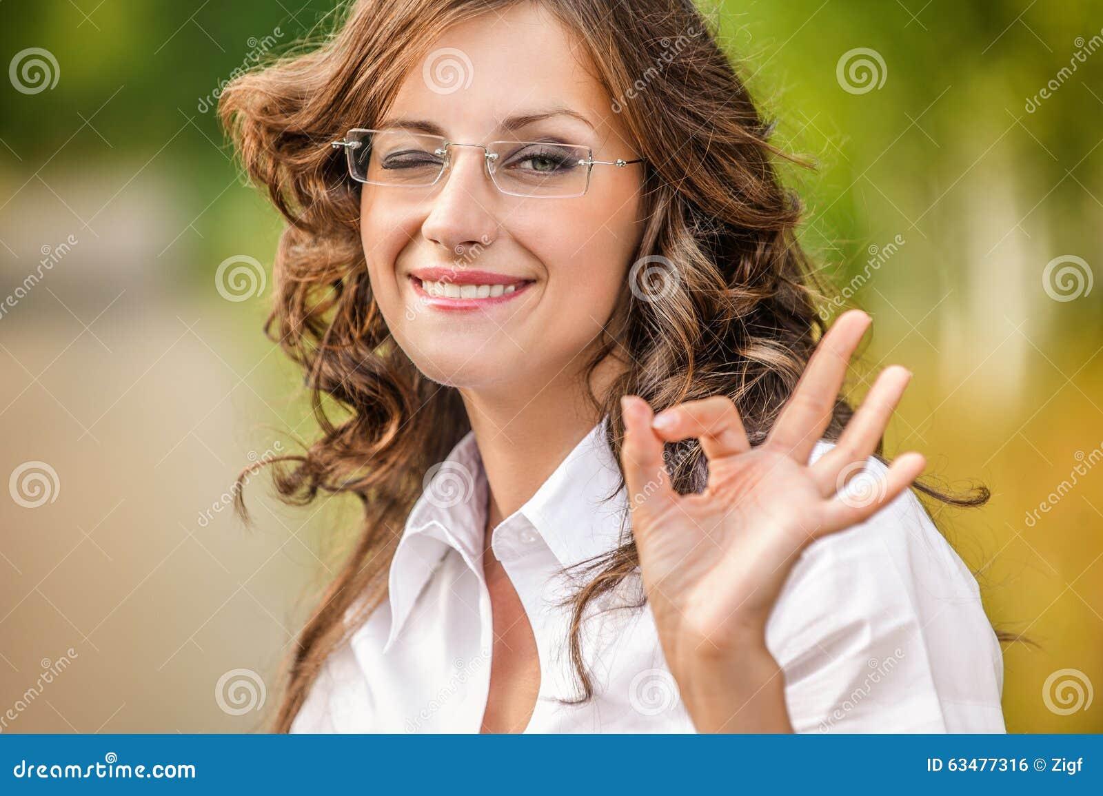 Vitória encantador do sinal das mostras dos vidros da jovem mulher do retrato