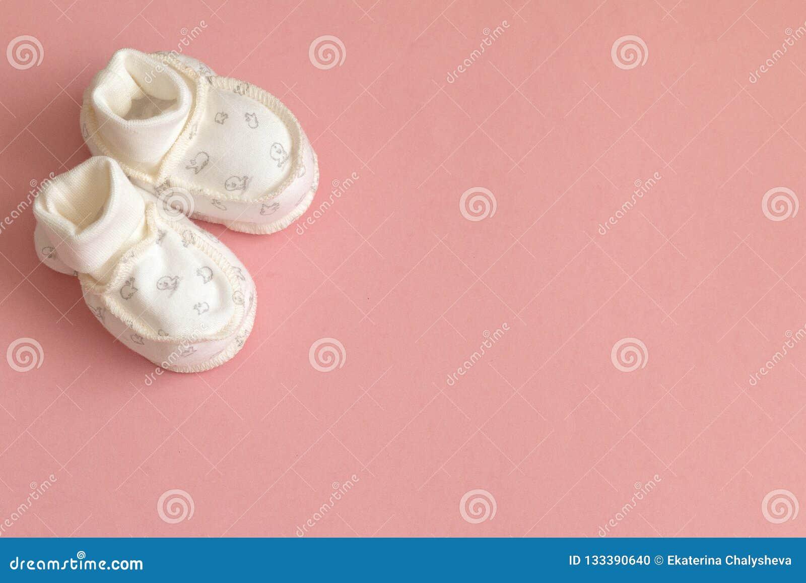 Vit babys barnsockor på rosa bakgrund