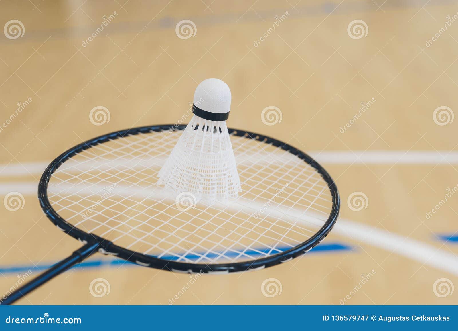 Vit badmintonfjäderboll på ett hallgolv på badmintondomstolar Stäng sig upp fjäderbollar på racketbadminton på badmintondomstolar