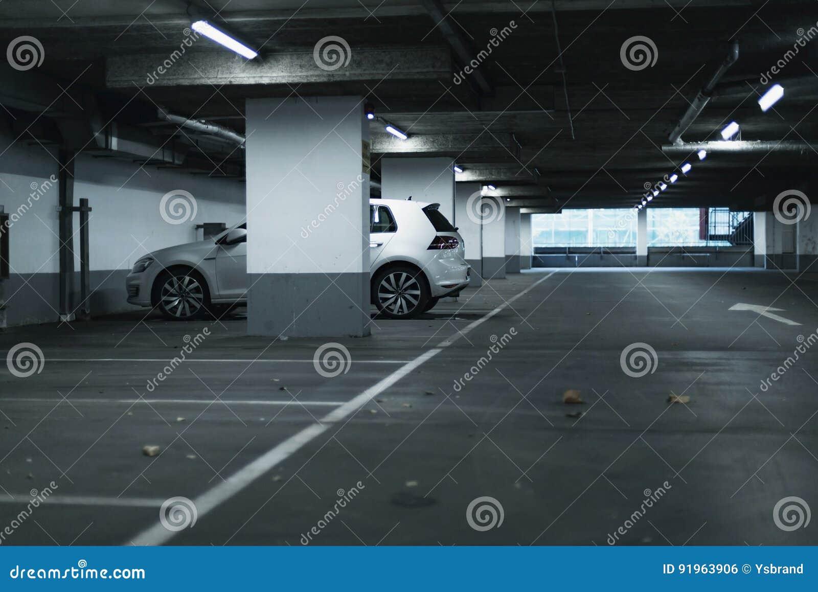 Vit bil som parkeras i tomt parkeringsgarage