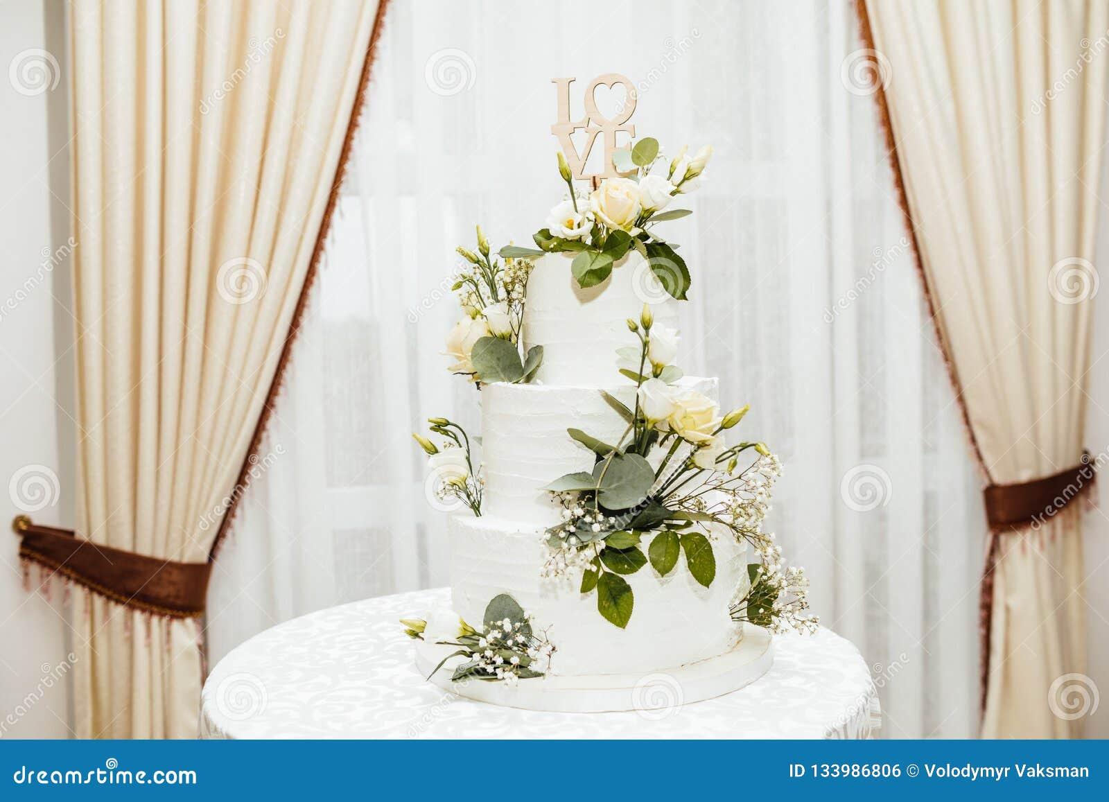 Vit bröllopstårta med blommor Ordförälskelsen med hjärta