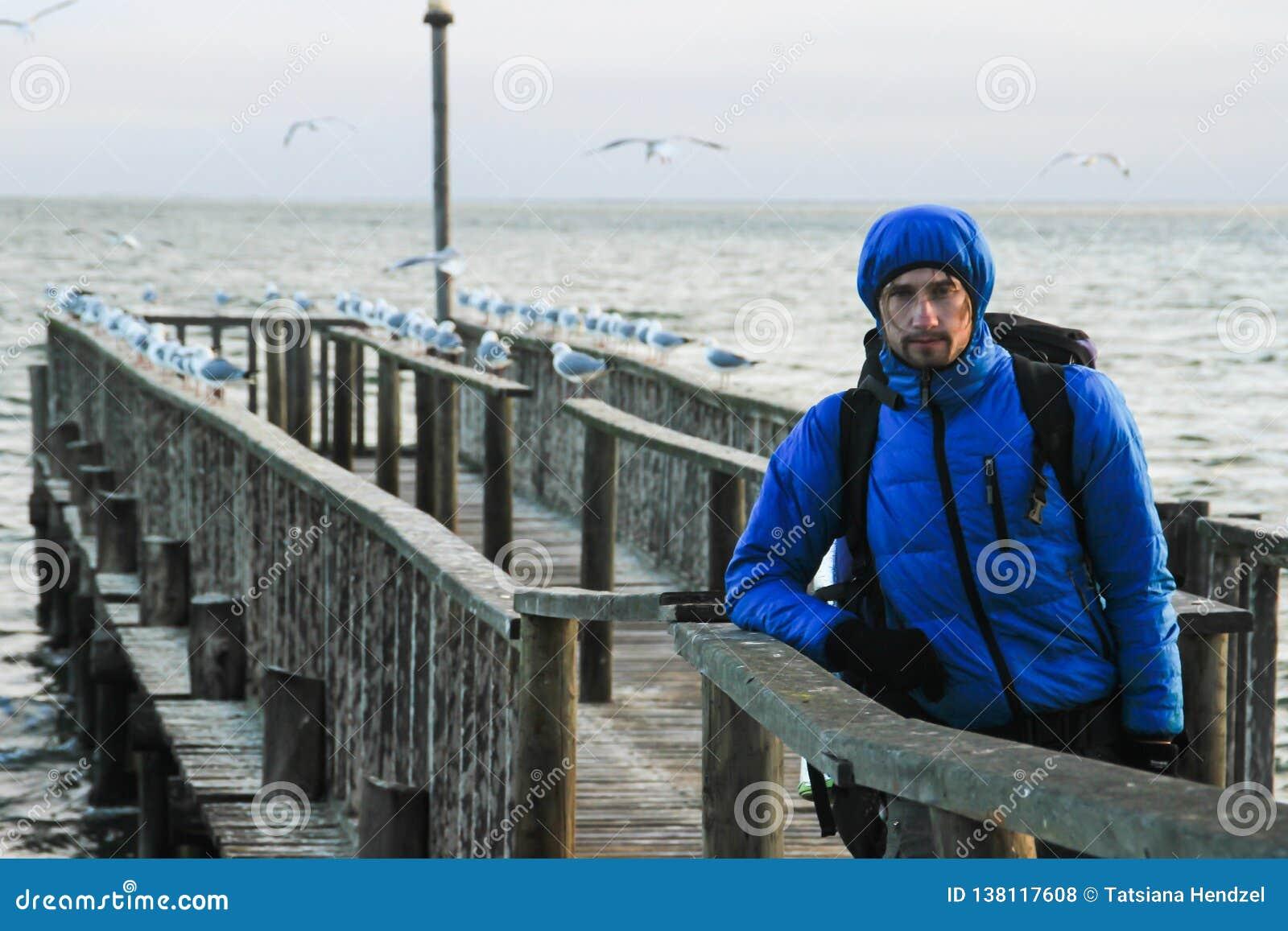 Vit Caucasian manlig handelsresande i ett blått omslag för sportar, handskar, hatt, exponeringsglas och ett ryggsäckanseende på p