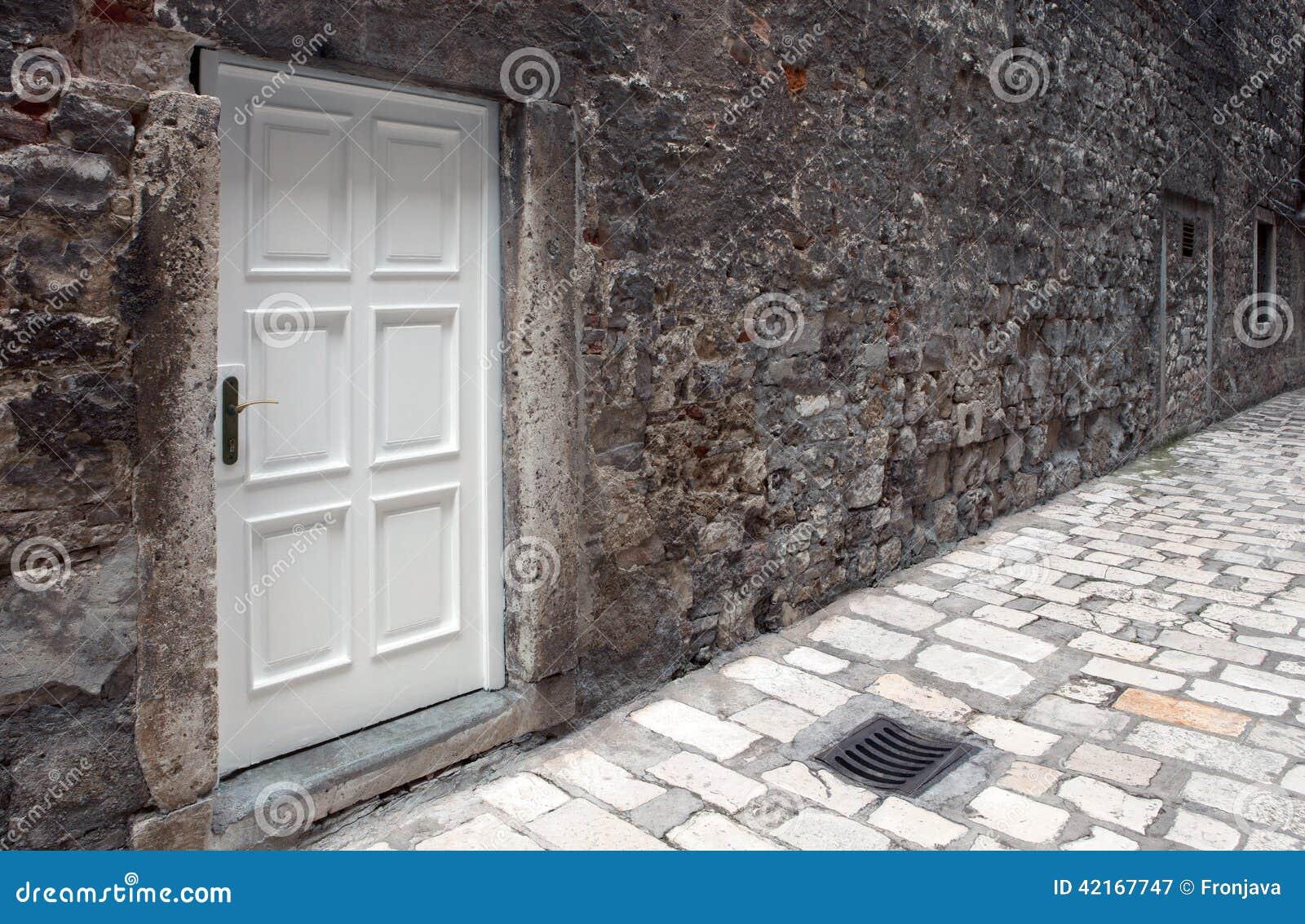 Vit dörr på den förstörda väggen