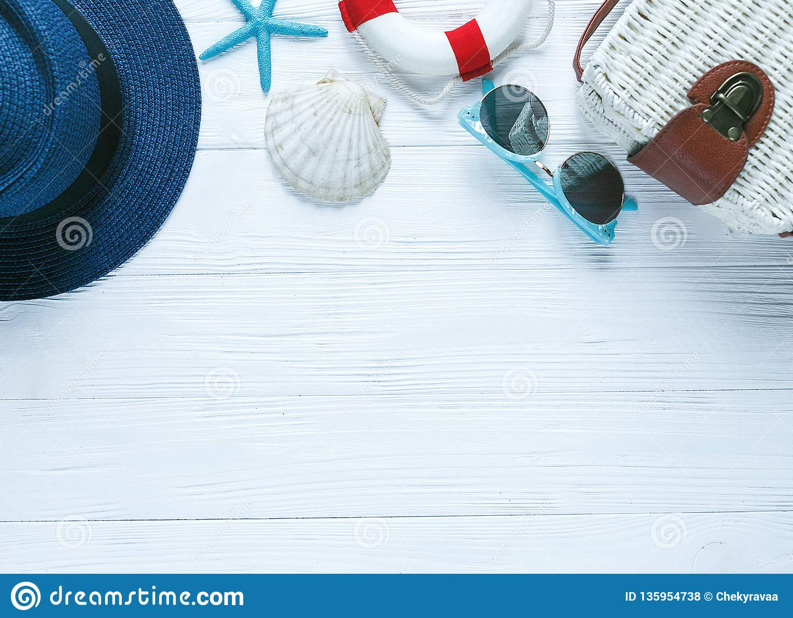 Vit ecorottingpåse, sjöstjärnaskalsolglasögon och en kvinnas blåa hatt på den vita trätabellen Sommarbakgrund, semestrar, lopp