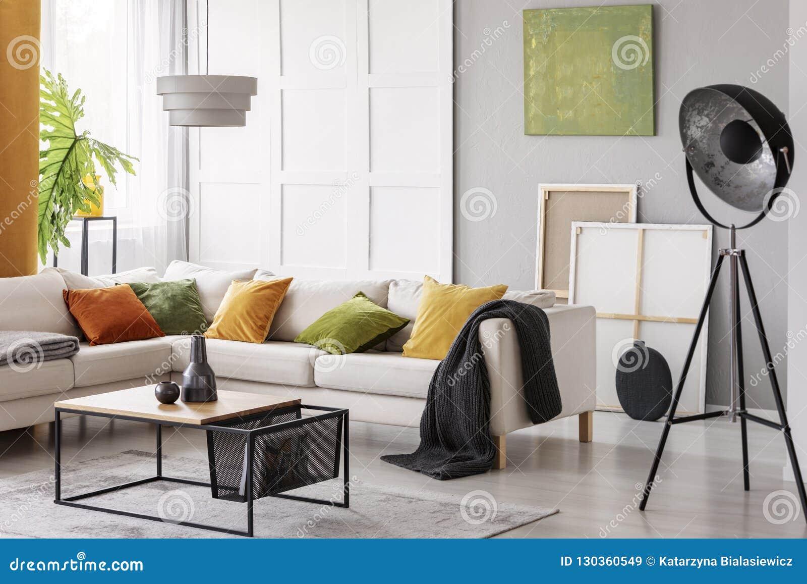 Vit elegant hörnsoffa med orange gröna och gula kuddar i stilfull vardagsrum som är inre med den modern kaffetabellen och indust
