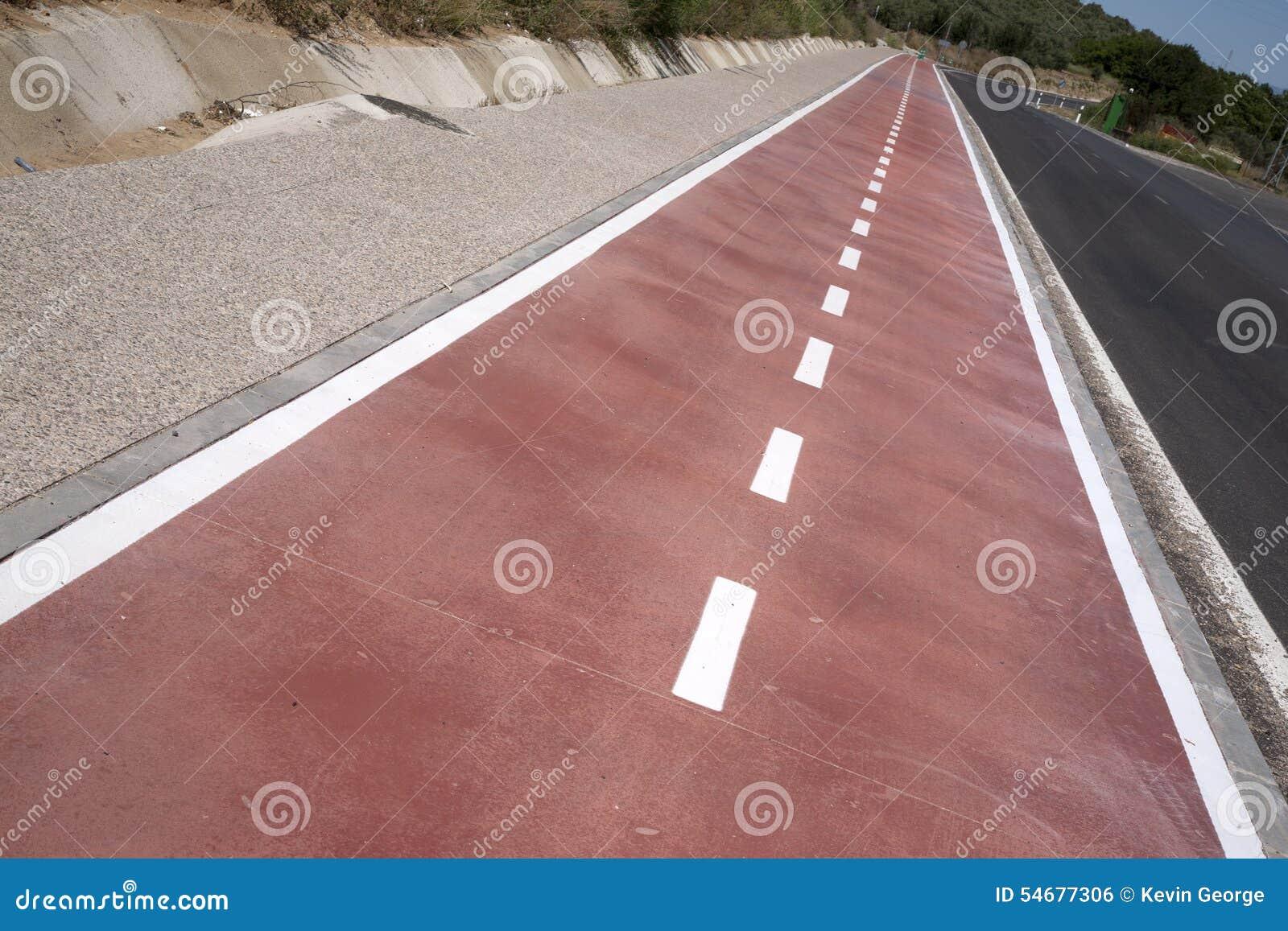 Vit fläck av cykel- och vitpilen som pekar en väg på asfaltbanan