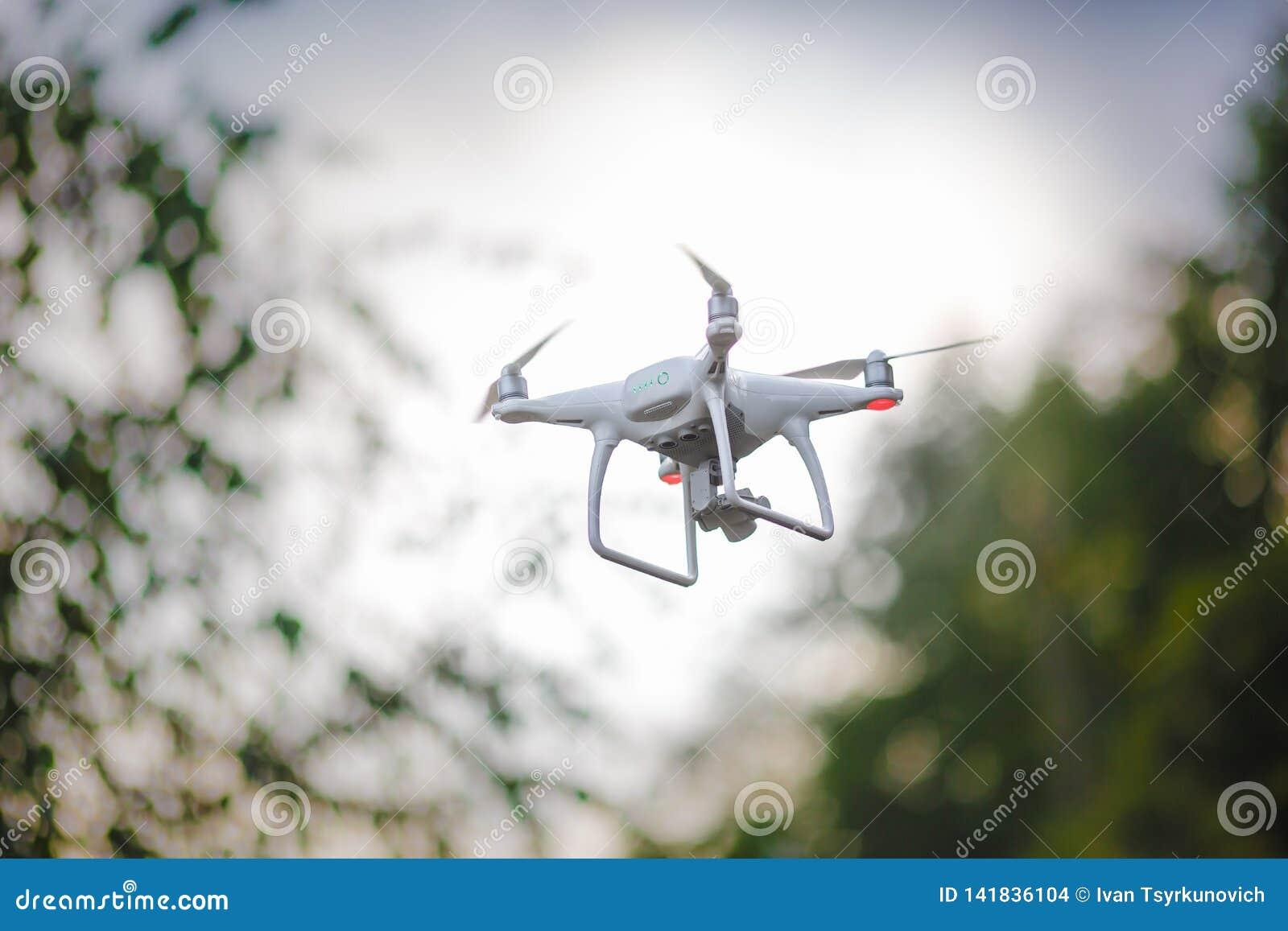 Vit flygaquadrocopter med kameran på grön skogbakgrund