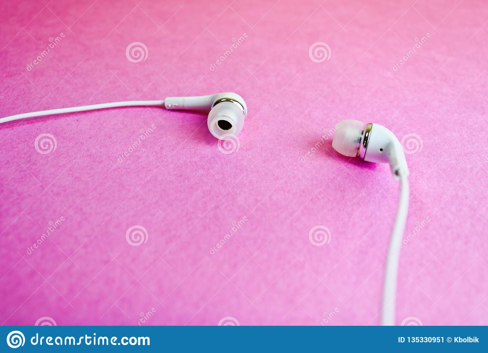Vit hörlurar för härligt modernt digitalt plast- vakuum med trådar för att lyssna till musik på en purpurfärgad rosa bakgrund kop