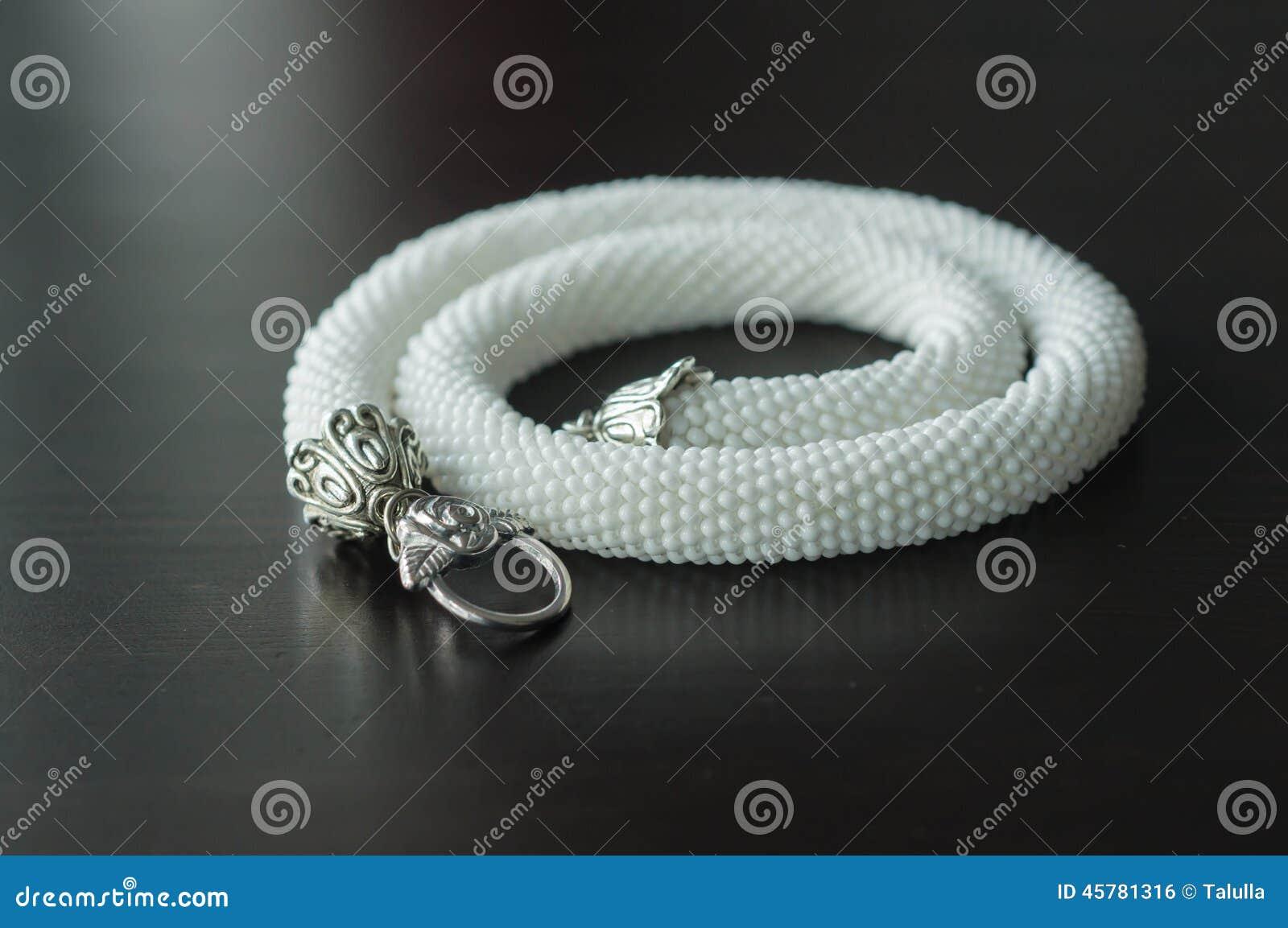Vit halsband från pärlor på en träbakgrund