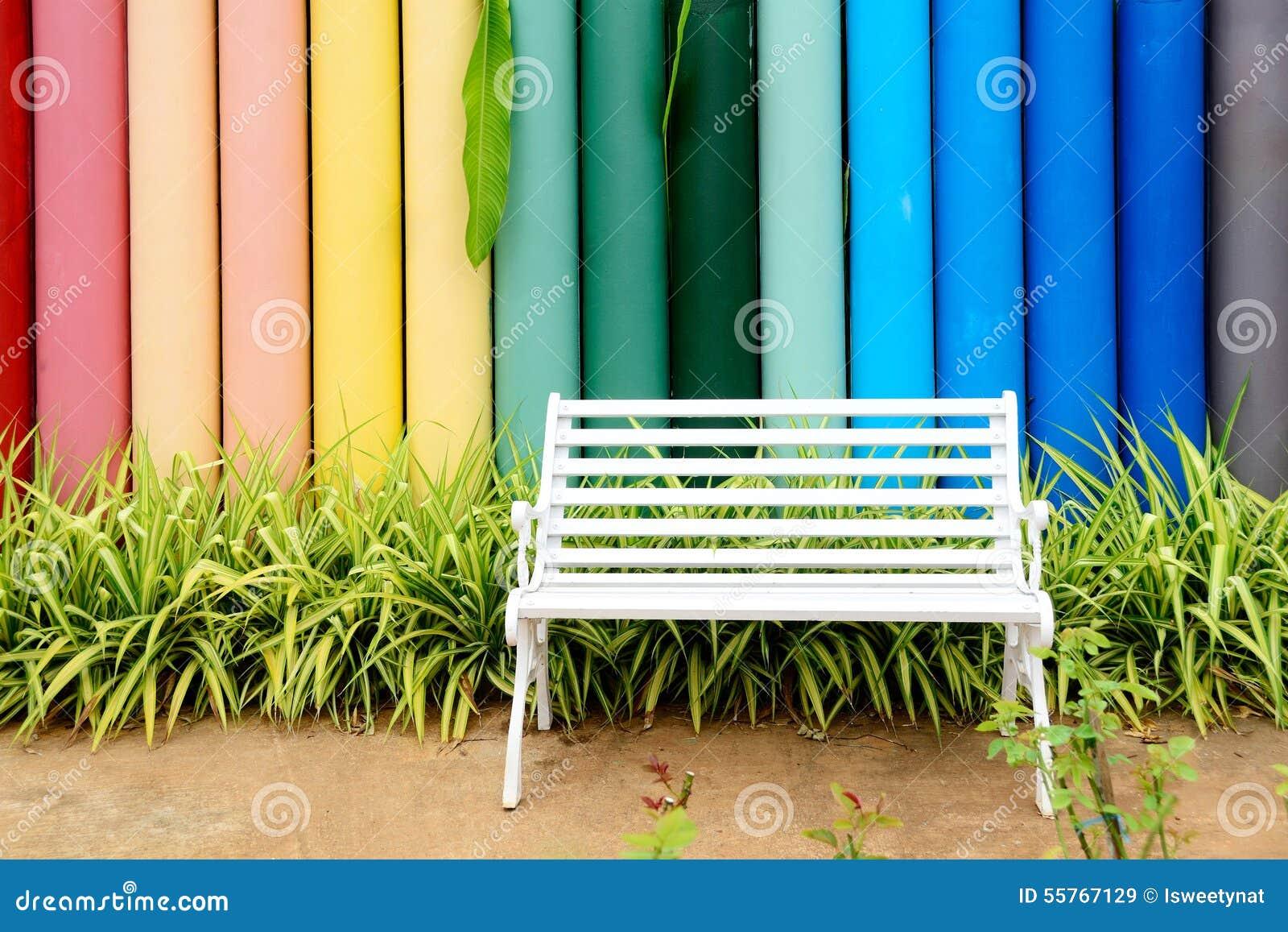 Vit järnbänk och flerfärgat konkret staket arkivfoto   bild: 55767129