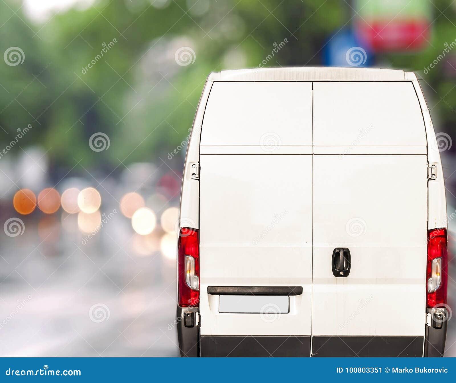 Vit körning för leveransskåpbil som är snabb på gatan för stadsblurrbokeh