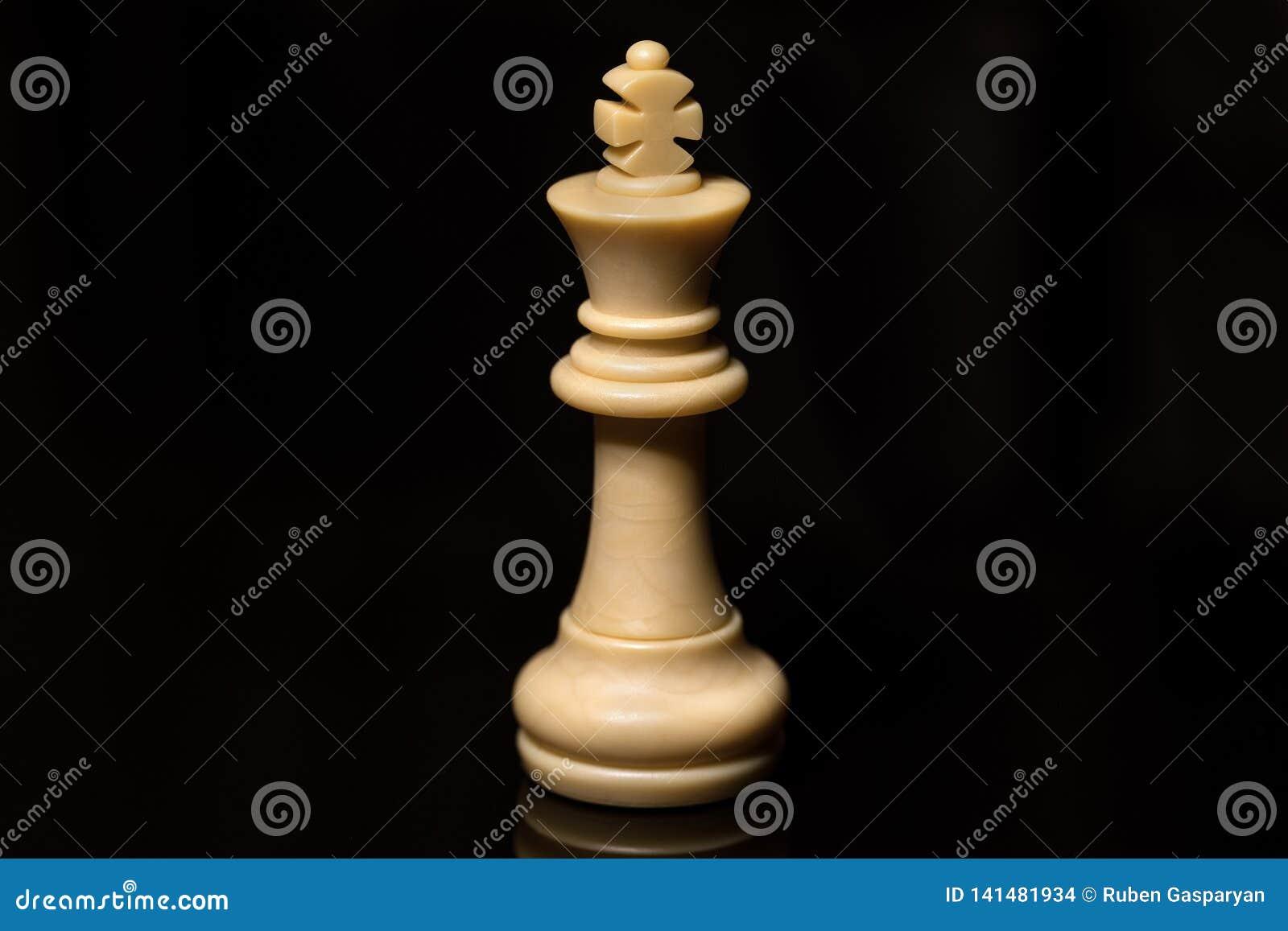 Vit konung för klassiskt schack på det svarta brädet som isoleras
