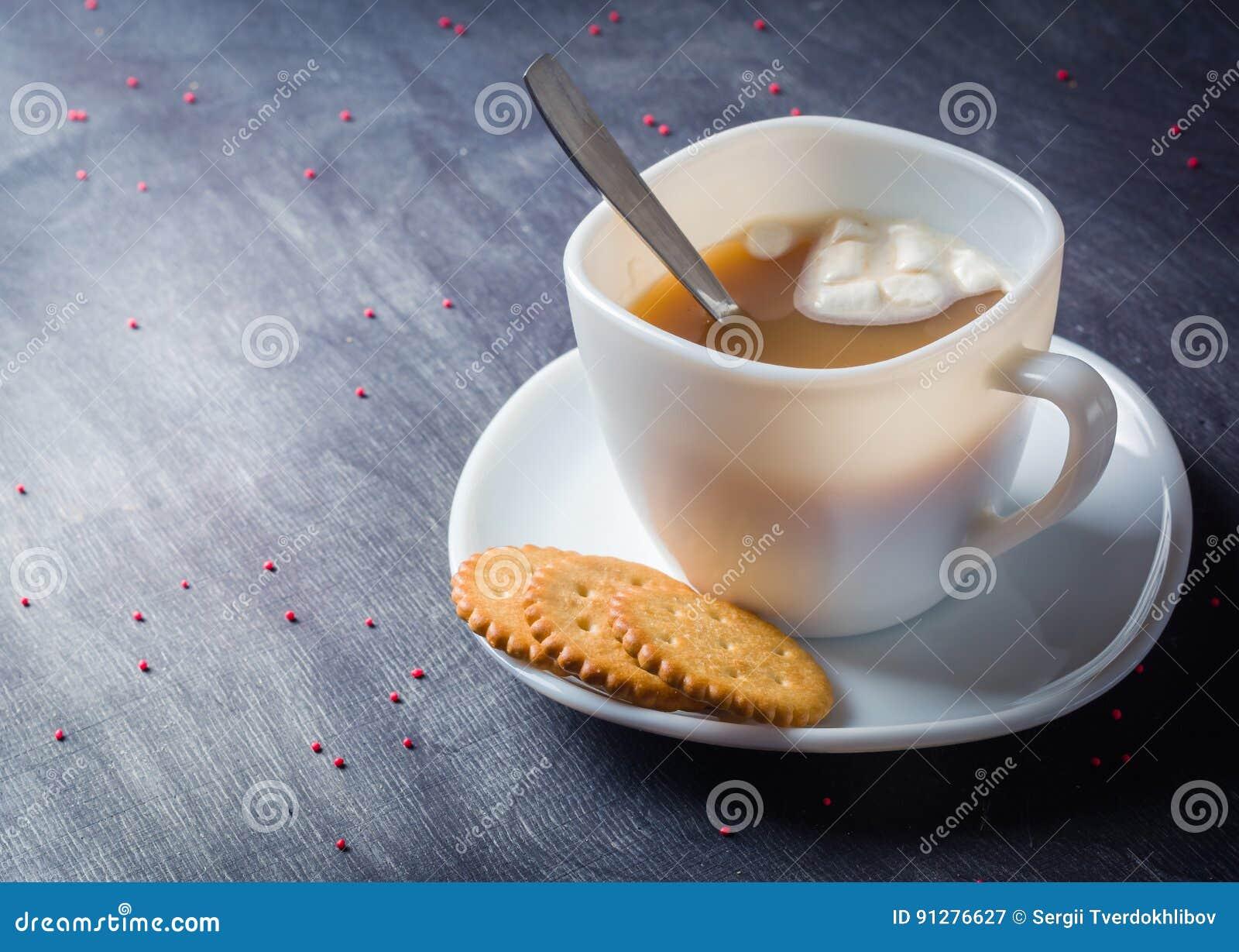 Vit kopp på ett tefat med varm kakao Mörk träbakgrund för morgonfrukost
