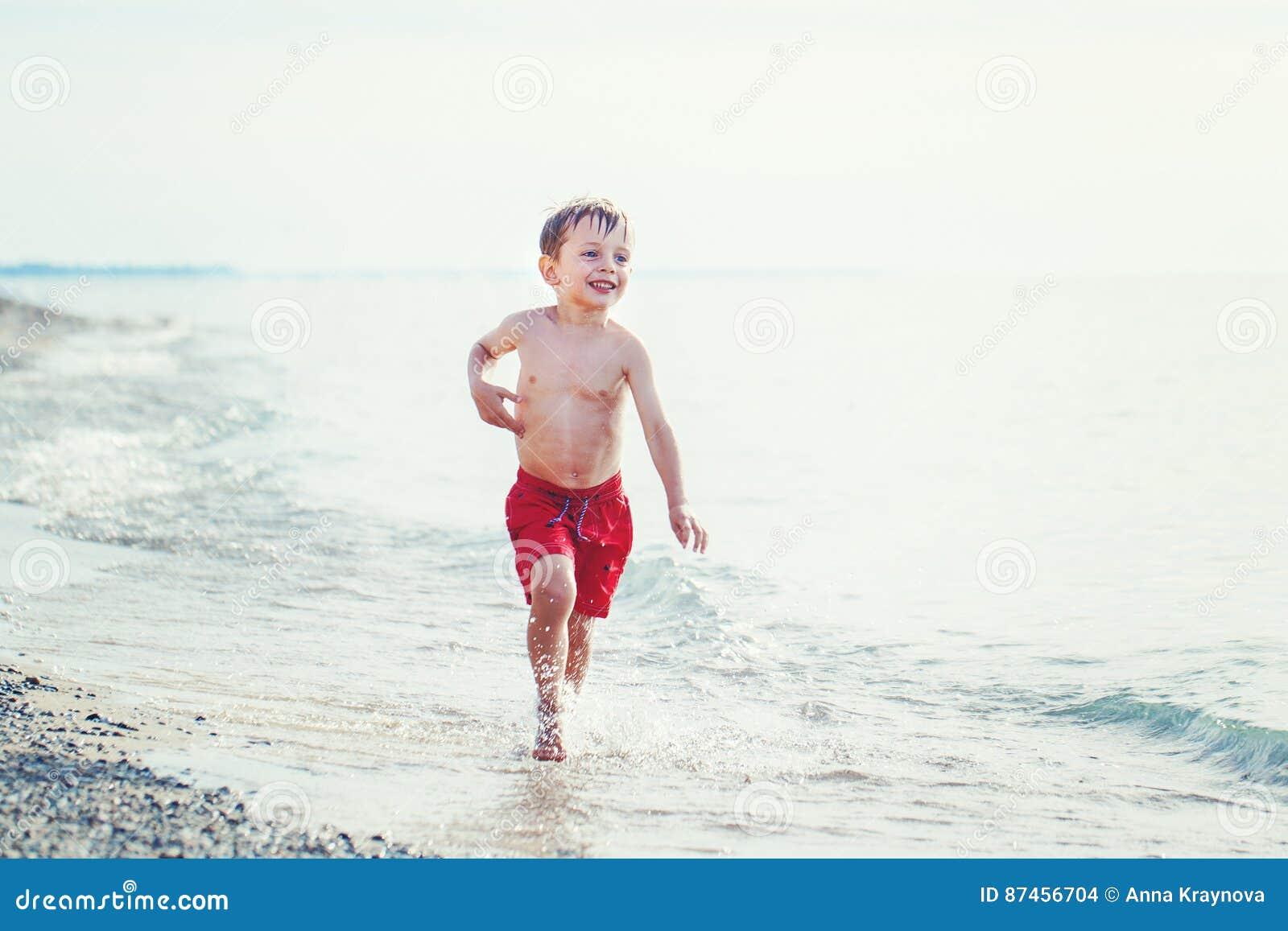 Vit kortsluter den unga pysen för Caucasian i rött bad spring på stranden vid vatten