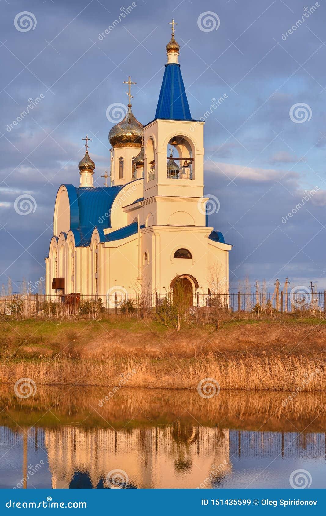 Vit kyrka med det blåa taket på sjön