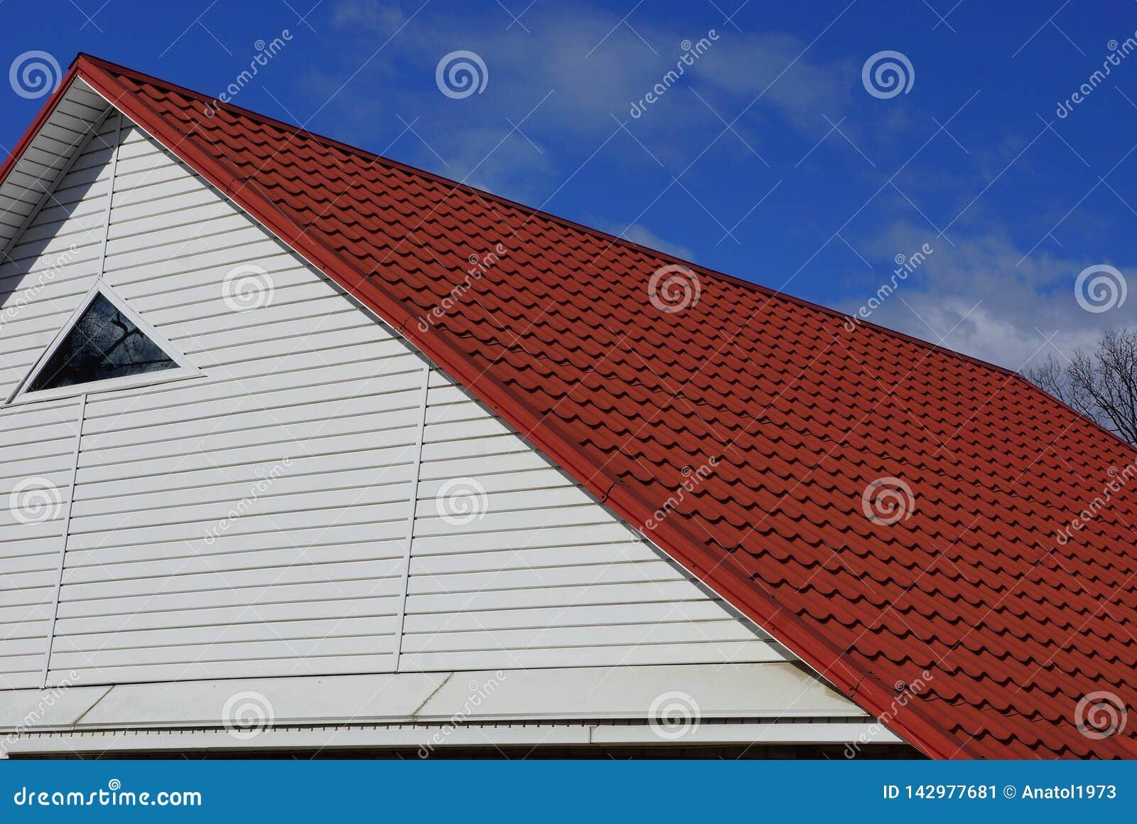 Vit loft med ett litet fönster under taket för röd tegelplatta mot himlen och molnen