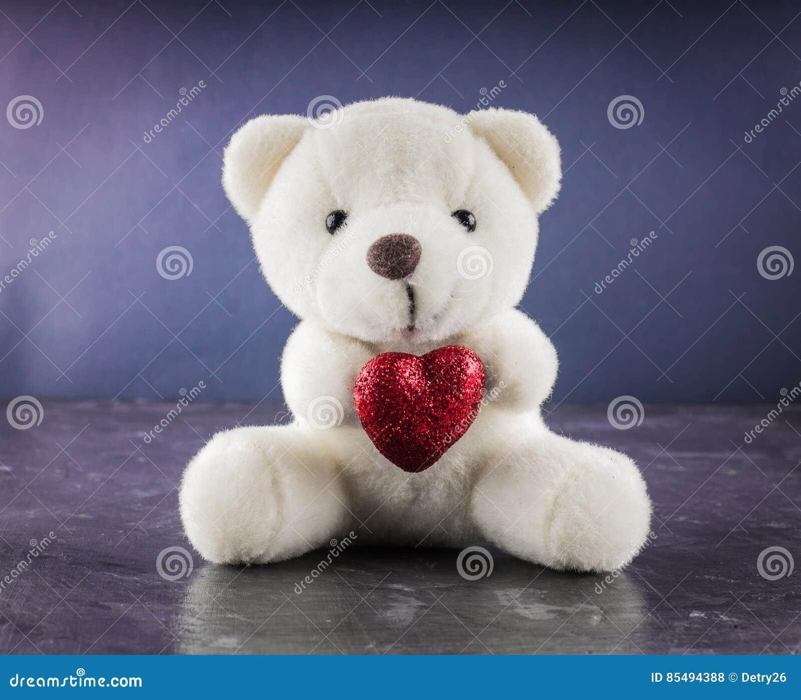 Vit nallebjörn med förälskelsebokstaven på röd hjärtagrå färgbakgrund Säg I dig för begrepp för dag för valentin` s